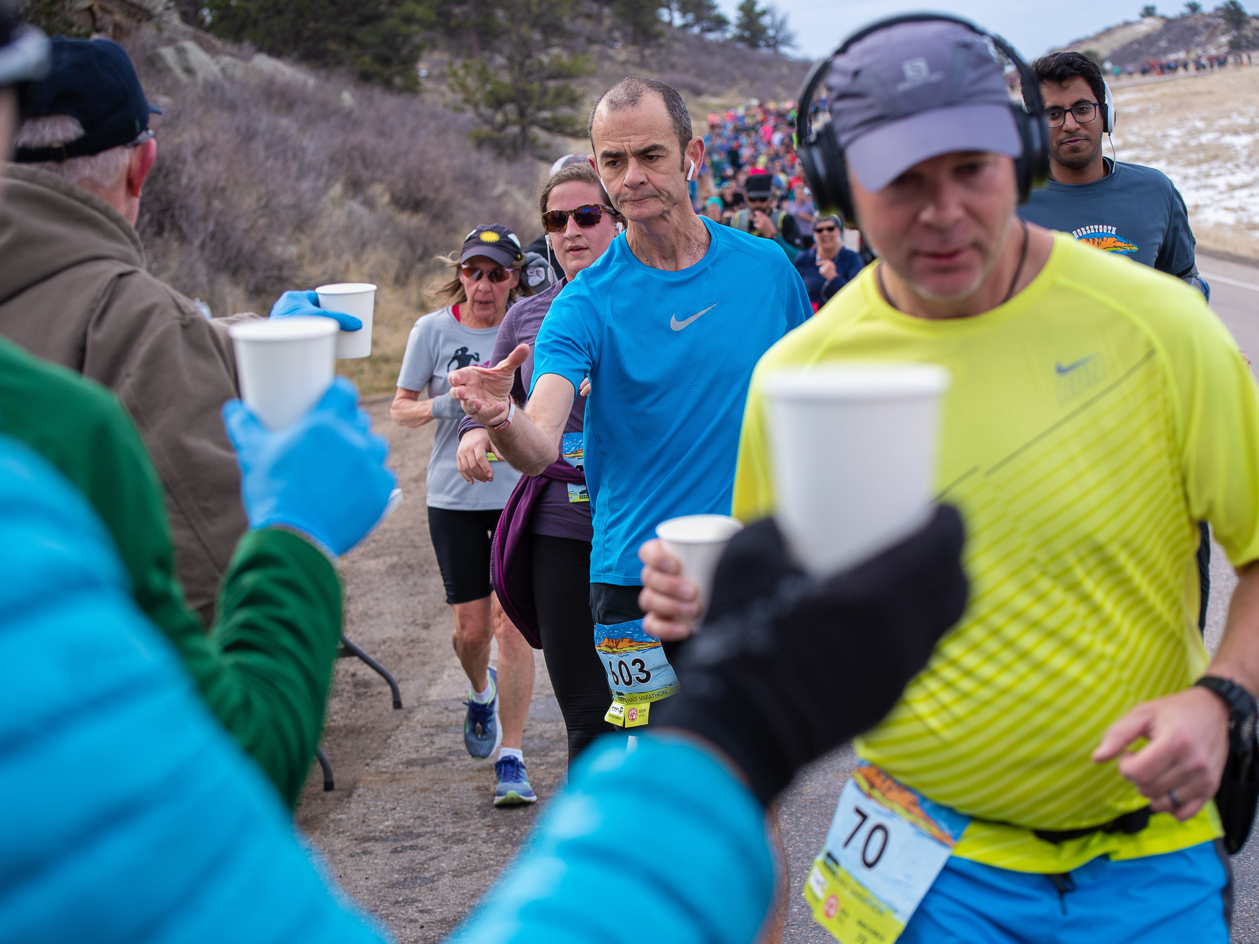 Runners slow down for water at a first aid station along the route of the Horsetooth Half Marathon on Sunday, April 14, 2019, in Fort Collins, Colo.