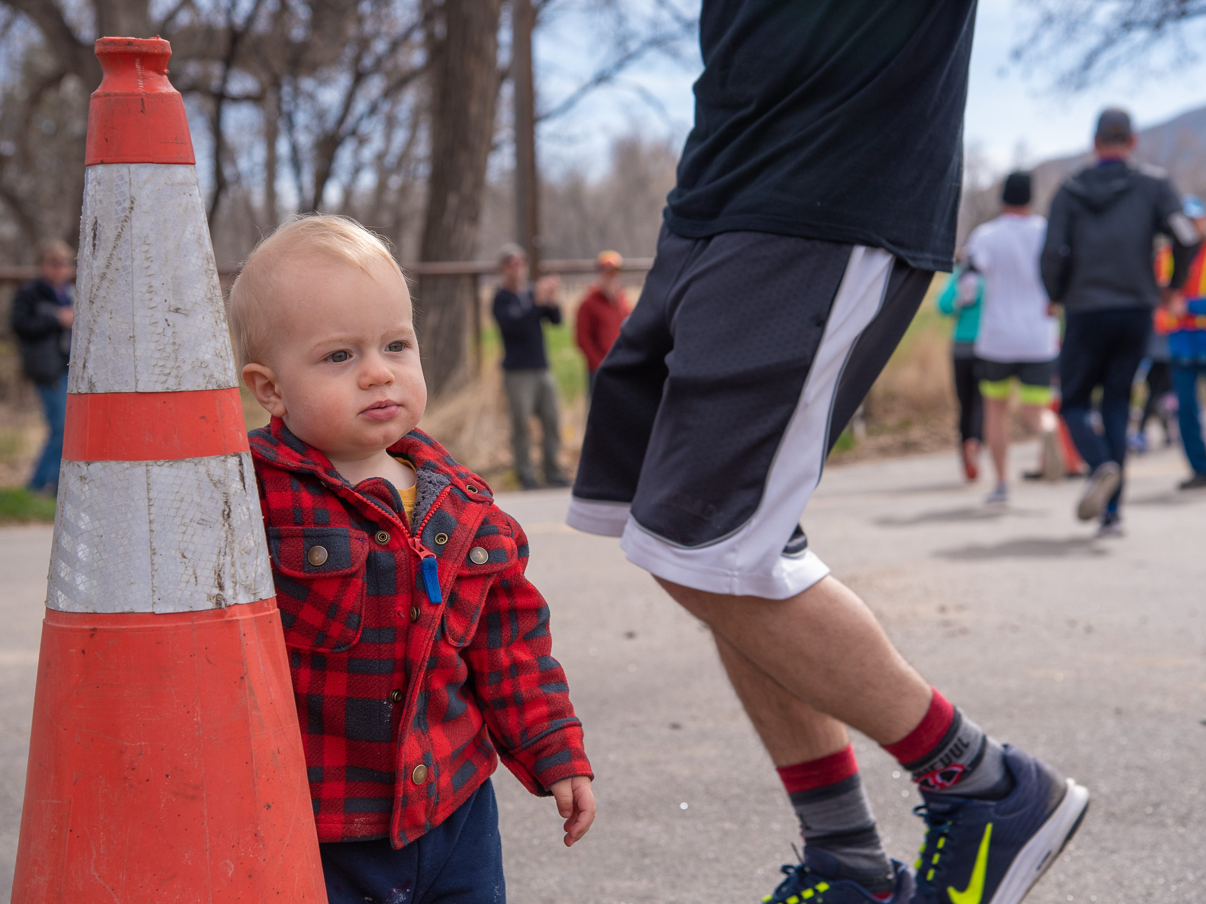 Jude Veliquette, 1,  watches race participants near the corner of Bingham Hill Road during the Horsetooth Half Marathon on Sunday, April 14, 2019, in Fort Collins, Colo.