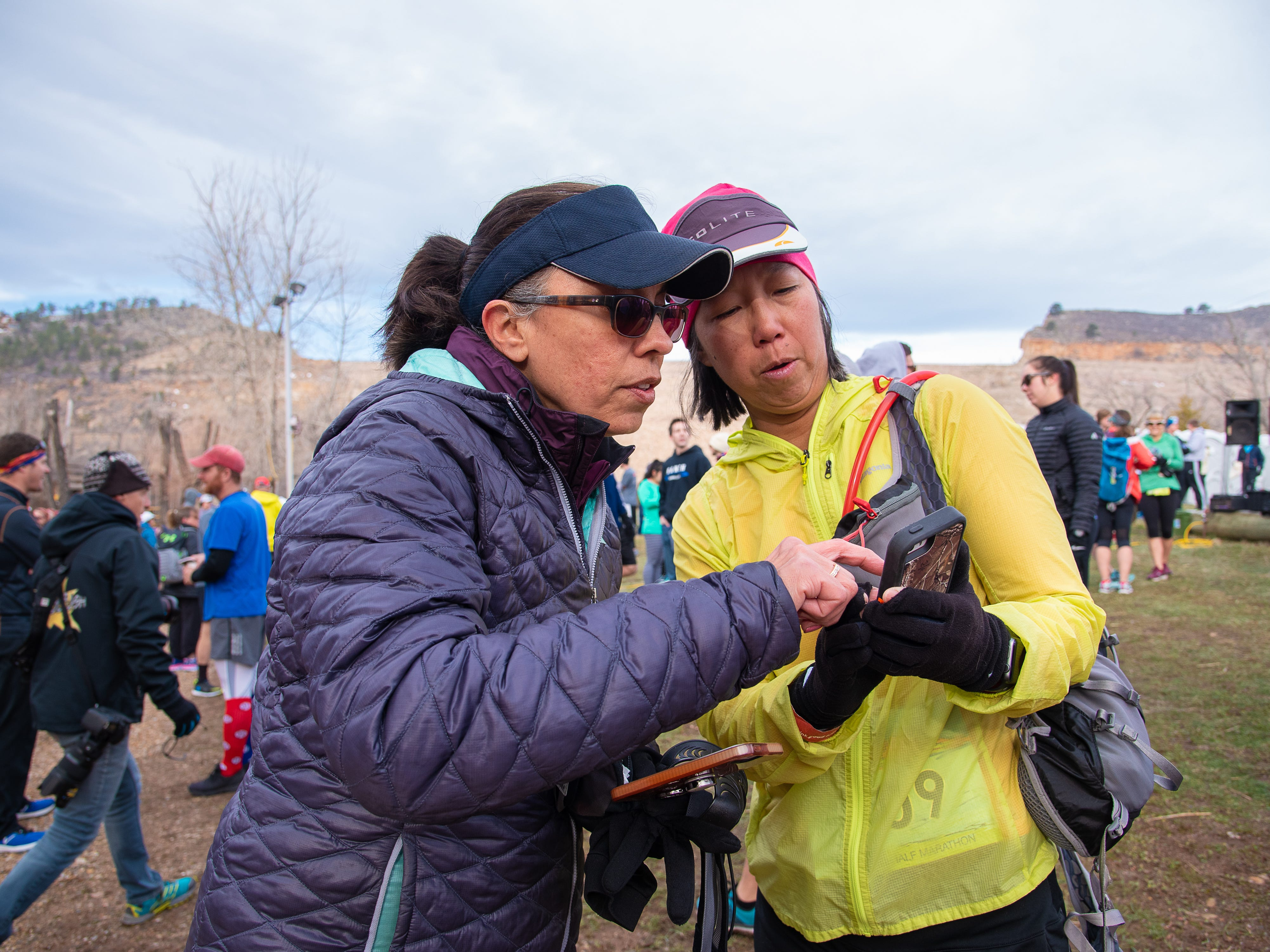 Participants Andrea Opper and Connie Hannig coordinate an app on their phones before the start of the Horsetooth Half Marathon on Sunday, April 14, 2019, in Fort Collins, Colo.