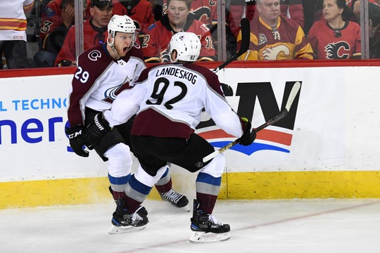 Nathan MacKinnon, left, of the Colorado Avalanche celebrates his winning goal in overtime Saturday night with teammate Gabe Landeskog, tying the team's first-round playoff series with Calgary at 1-1.  Game 3 is at 8 p.m. Monday at the Pepsi Center in Denver.