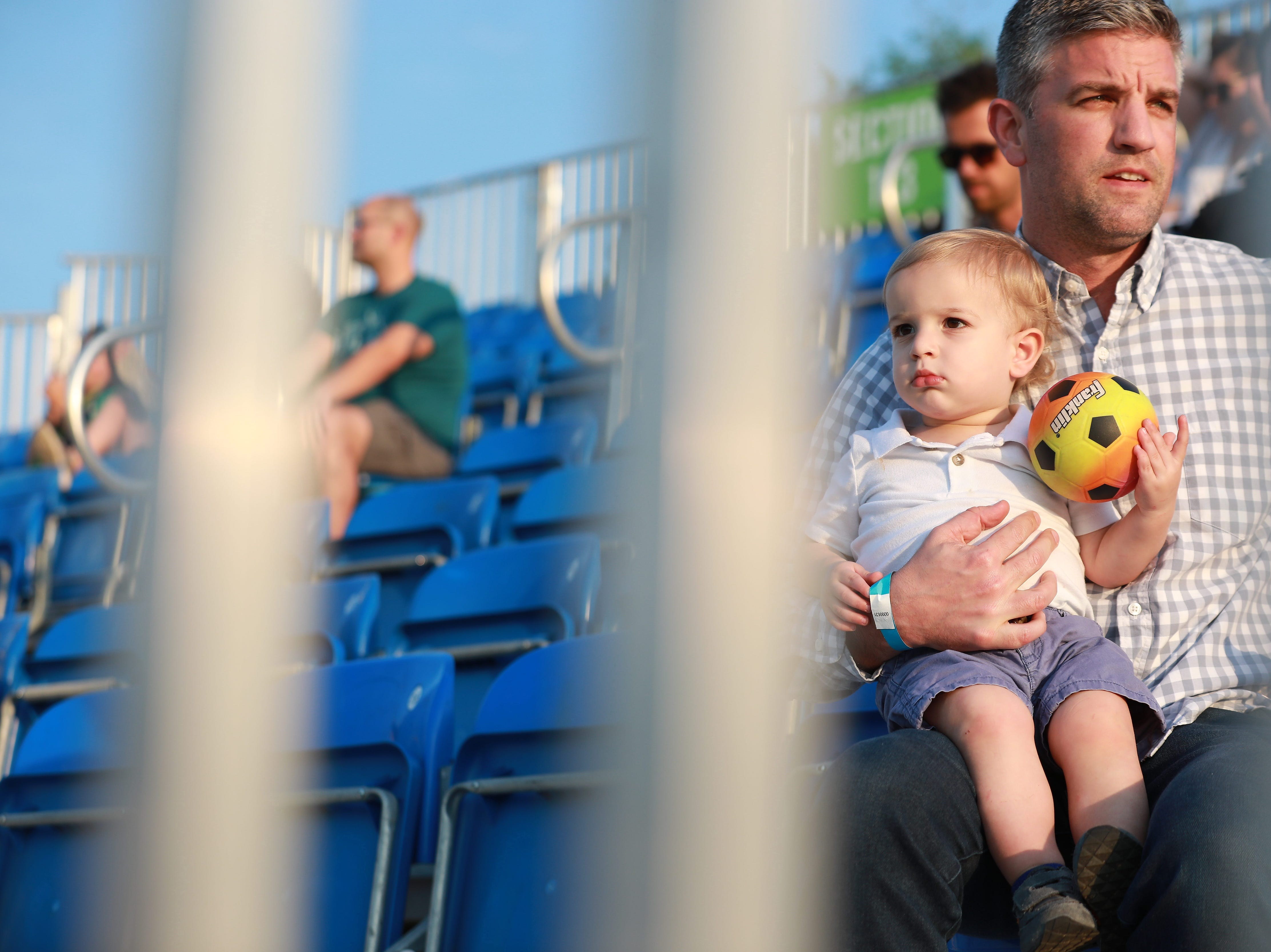 Lucas Ouellette, 1, and his dad, Cory, watch from the stands at the Greenville Triumph Soccer Club's second home game at Legacy Early College on April 13 against the Chattanooga Red Wolves.
