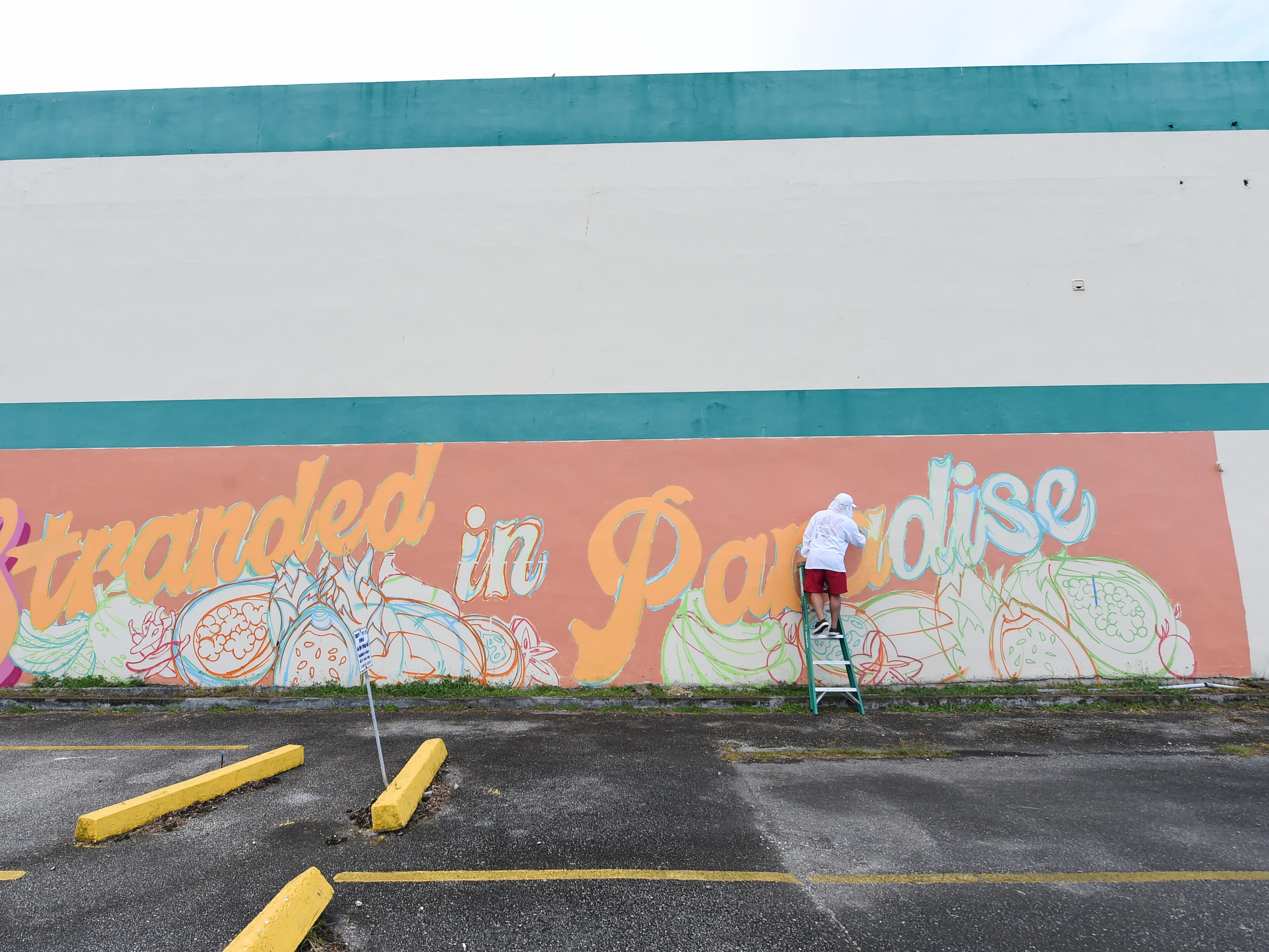 """Jerome Daco, an Opake Guam graphic artist, starts his company's """"Stranded in Paradise"""" mural for the GAX POW!WOW! Guam series in Hagåtña on April 14, 2019."""
