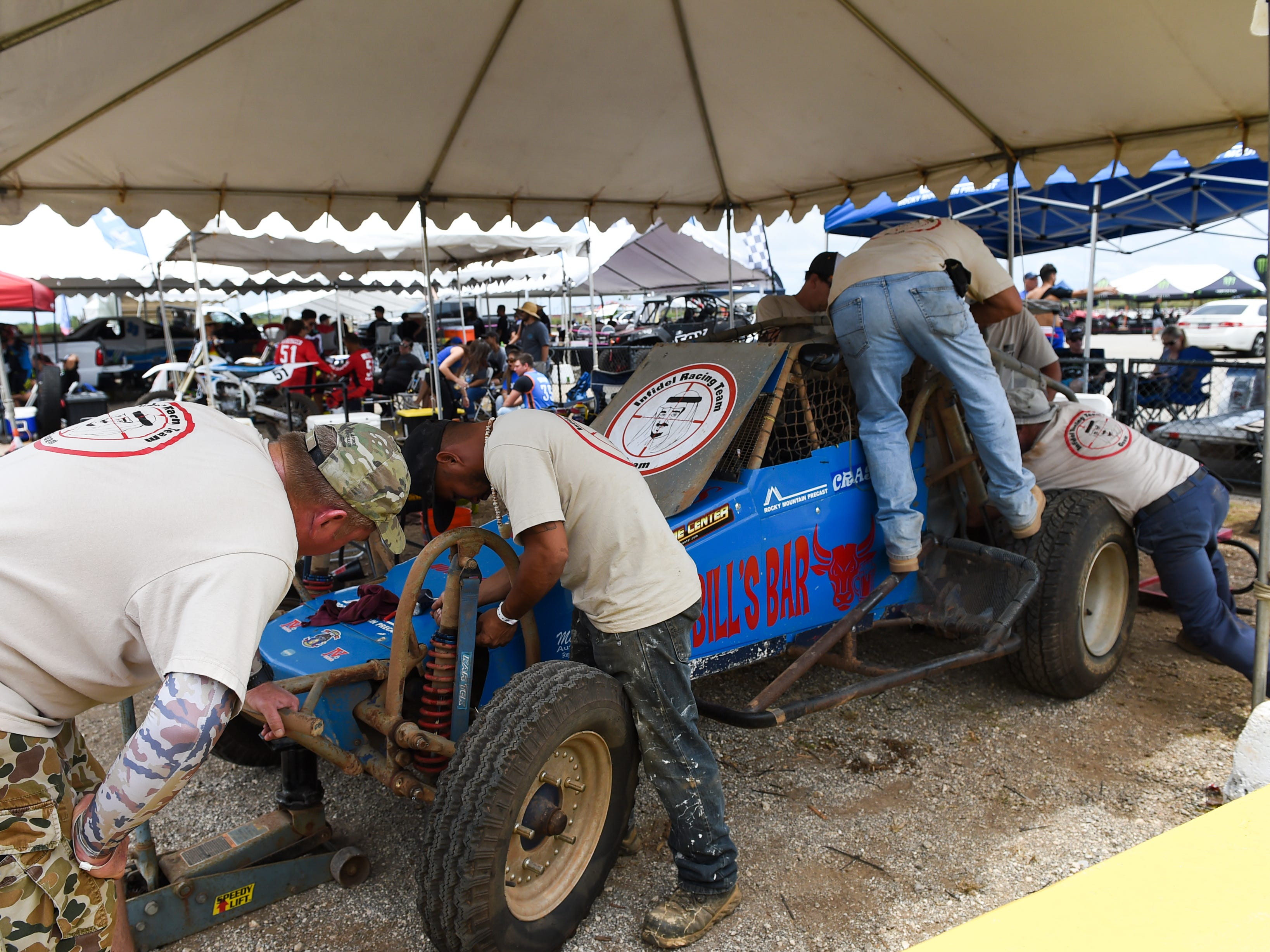 Infidel Racing Team Guam crew members work on one of their buggies during the 39th Annual APL Smokin' Wheels at the Guam International Raceway in Yigo, April 14, 2019.