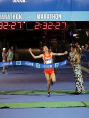 Yoshi Nakamura crosses the finish line with a time of 2 hours, 32 minutes and 31 seconds in the United Airlines Guam Marathon in this file photo. Concerns over the corona virus led organizers to postpone the event until Sept. 13.