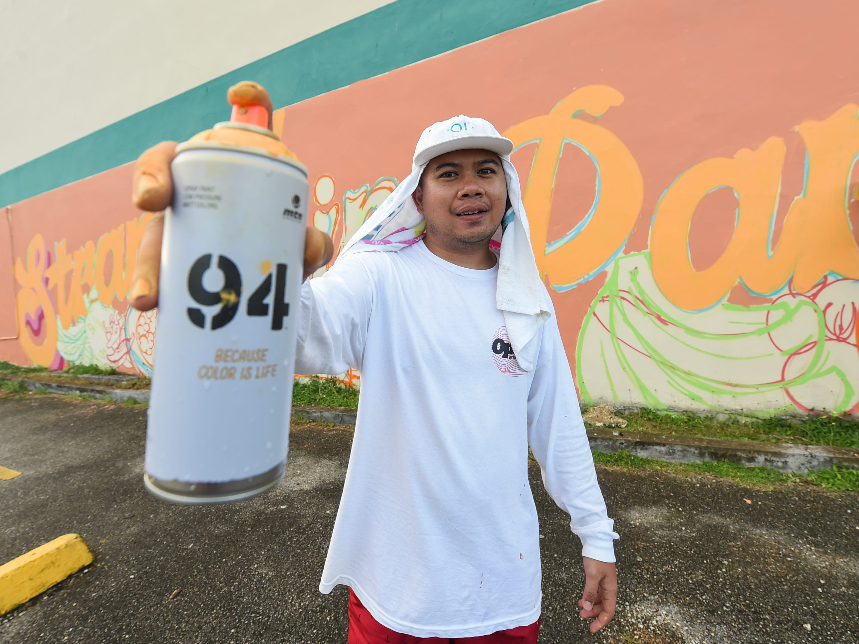 """Jerome Daco, an Opake Guam graphic artist, stands in front of his company's """"Stranded in Paradise"""" mural for the GAX POW!WOW! Guam series in Hagåtña on April 14, 2019."""