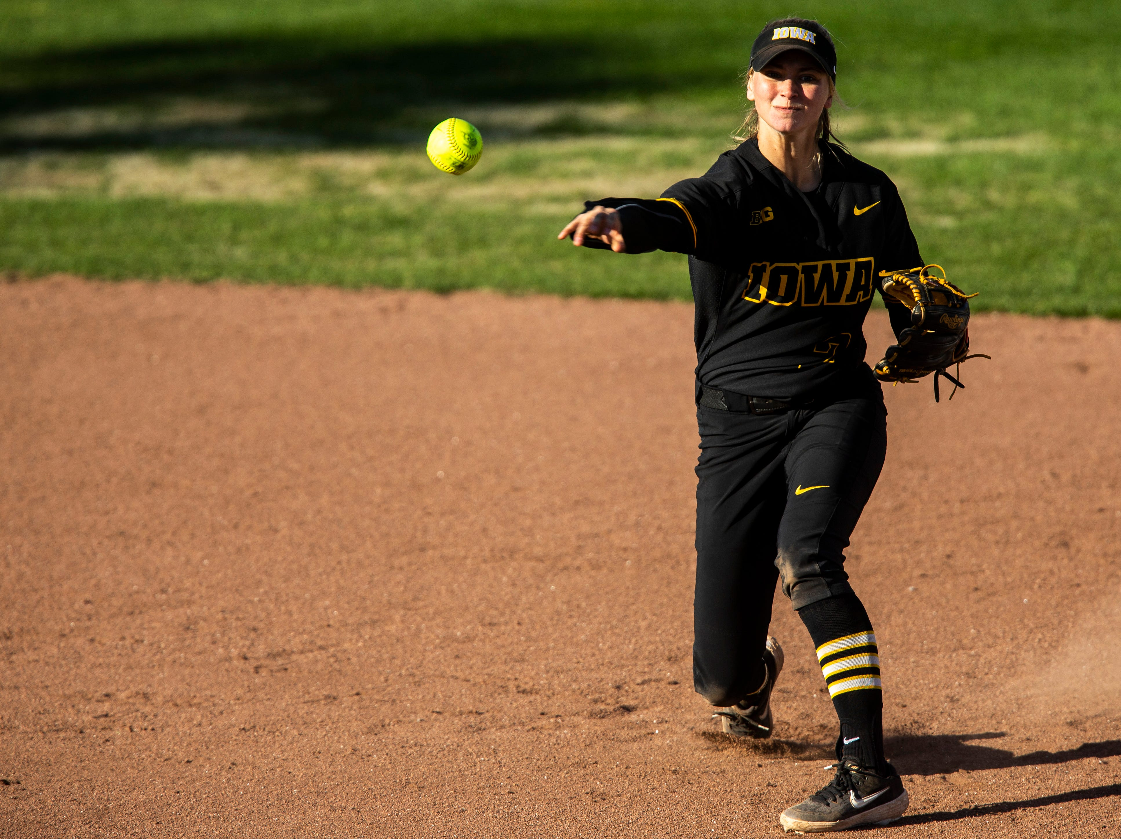Iowa utility player Aralee Bogar (2) throws to first after getting an out at second during a NCAA Big Ten Conference softball game on Saturday, April 13, 2019, at Bob Pearl Field in Coralville, Iowa.