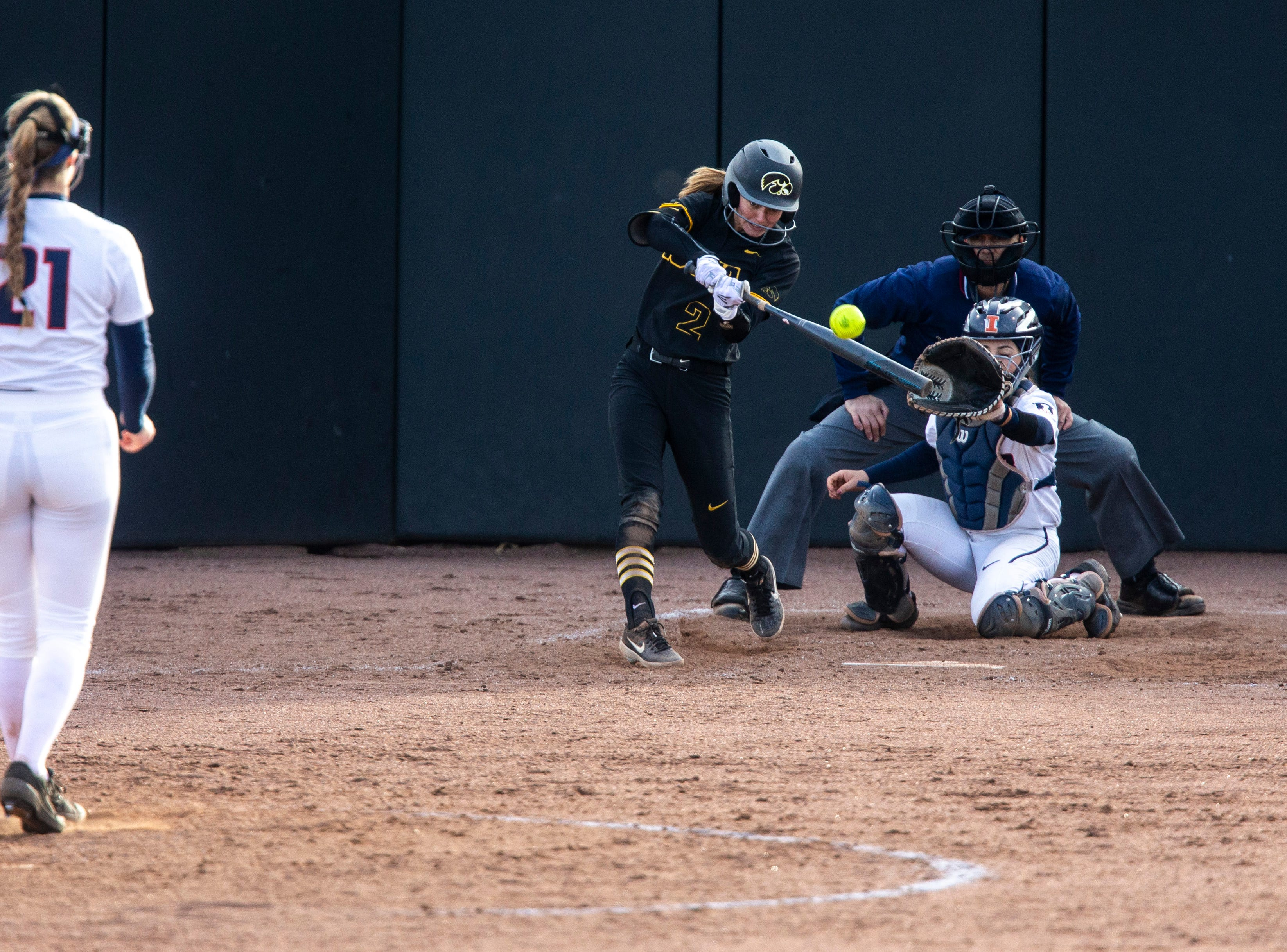 Iowa utility player Aralee Bogar (2) hits a double, batting in runners to tie the game, during a NCAA Big Ten Conference softball game on Saturday, April 13, 2019, at Bob Pearl Field in Coralville, Iowa.