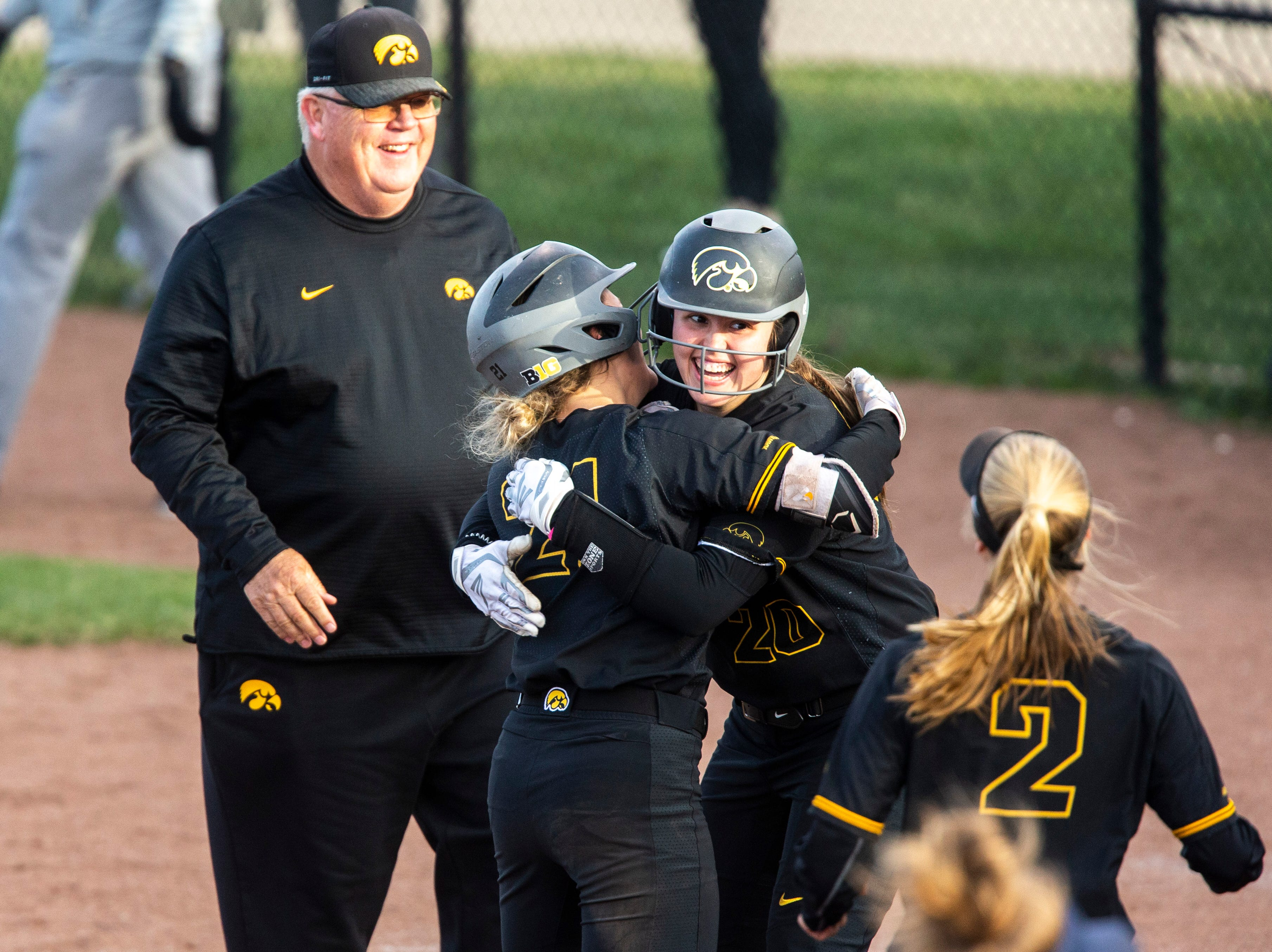 Iowa outfielder Havyn Monteer (21) gets embraced by teammate Iowa pitcher Miranda Schulte (20) after batting in a run for the win during a NCAA Big Ten Conference softball game on Saturday, April 13, 2019, at Bob Pearl Field in Coralville, Iowa. The Hawkeyes defeated Illinois, 4-3, for the first home win of the season.