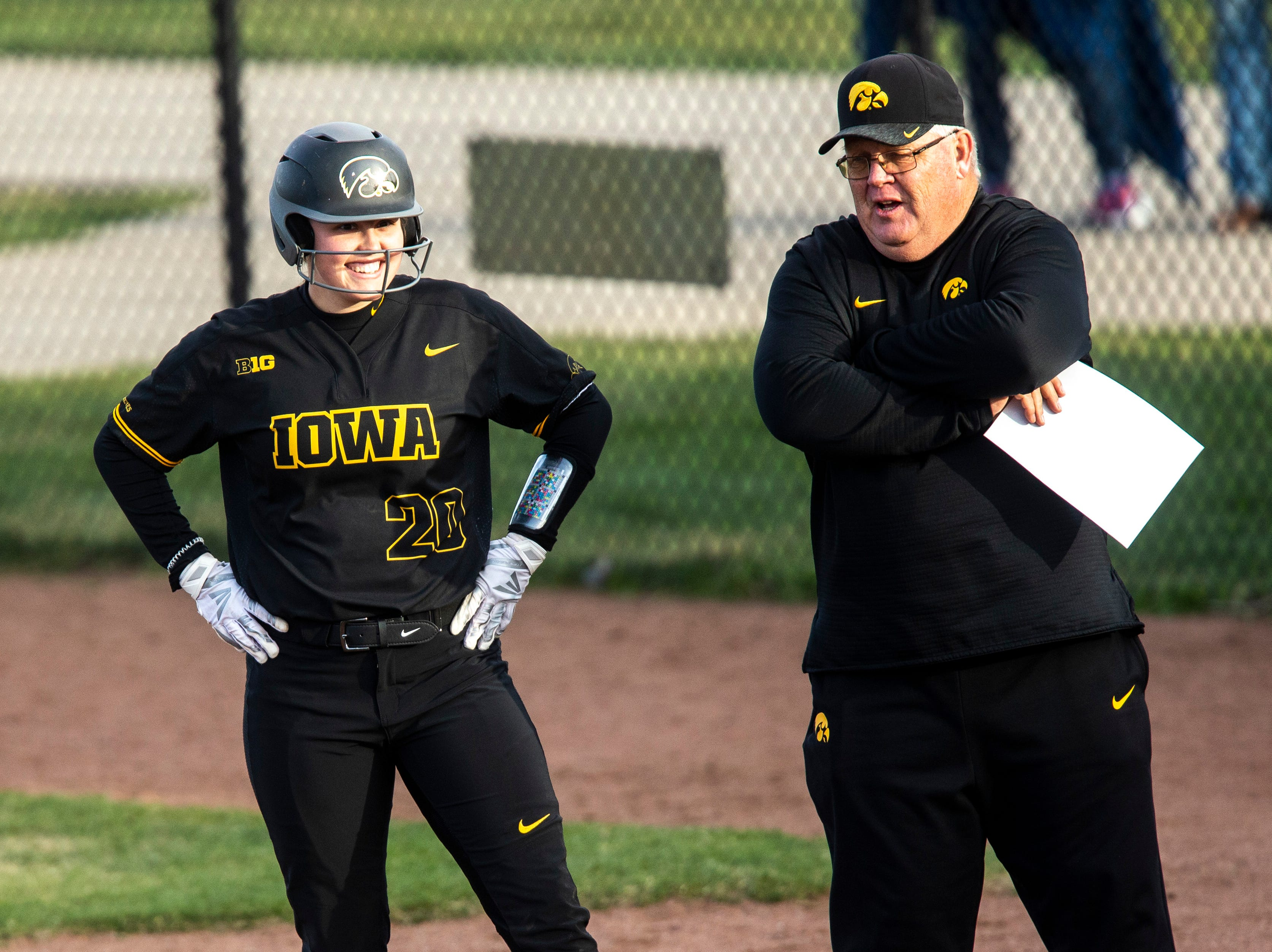 Iowa's Miranda Schulte (20) talks with assistant Rick Dillinger at first base during a NCAA Big Ten Conference softball game on Saturday, April 13, 2019, at Bob Pearl Field in Coralville, Iowa.