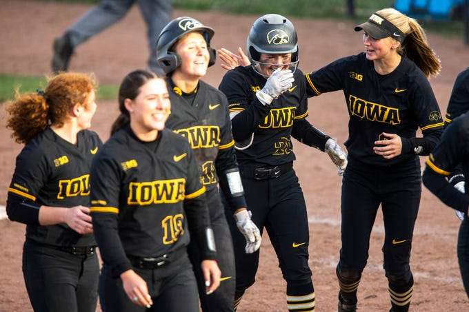 Iowa outfielder Havyn Monteer (21) is embraced by teammates including Aralee Bogar, right, after batting in a run for the win during a NCAA Big Ten Conference softball game on Saturday, April 13, 2019, at Bob Pearl Field in Coralville, Iowa. The Hawkeyes defeated Illinois, 4-3, for the first home win of the season.