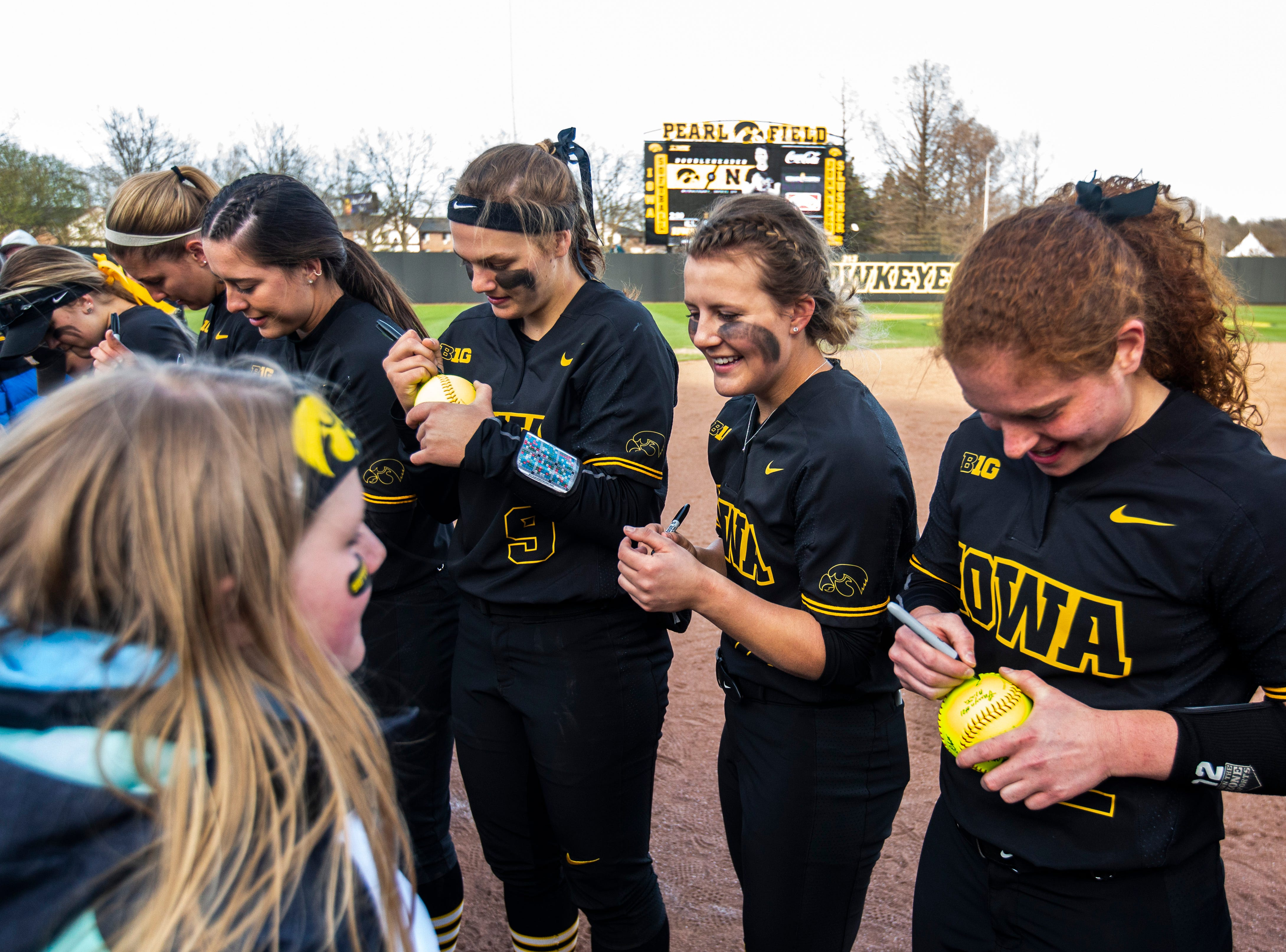 Iowa outfielder Havyn Monteer, second from right, signs a softball for a fan during a NCAA Big Ten Conference softball game on Saturday, April 13, 2019, at Bob Pearl Field in Coralville, Iowa. The Hawkeyes defeated Illinois, 4-3, for the first home win of the season.