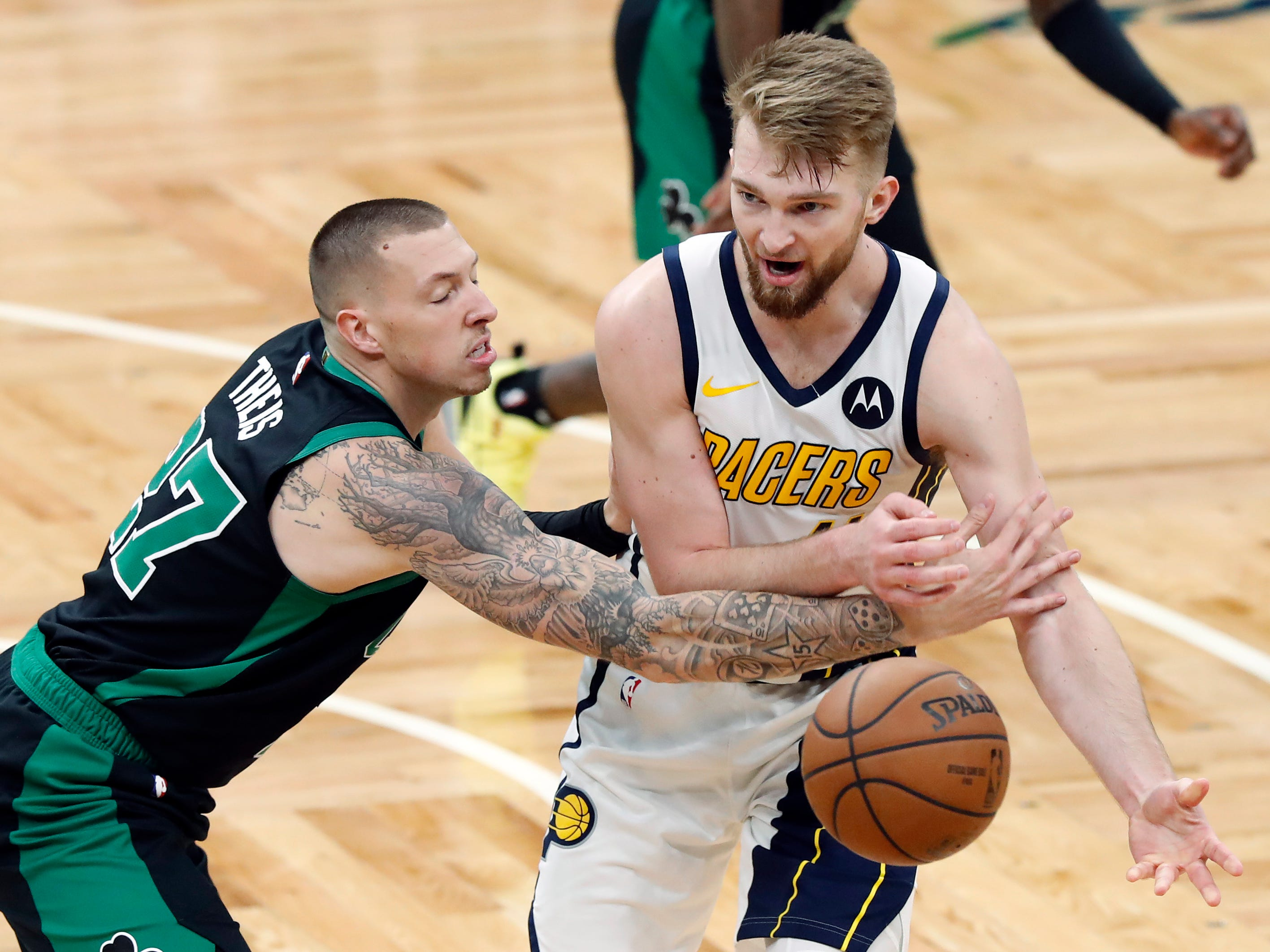 Boston Celtics' Daniel Theis, left, knocks the ball away from Indiana Pacers' Domantas Sabonis during the third quarter in Game 1 of a first-round NBA basketball playoff series, Sunday, April 14, 2019, in Boston. (AP Photo/Winslow Townson)