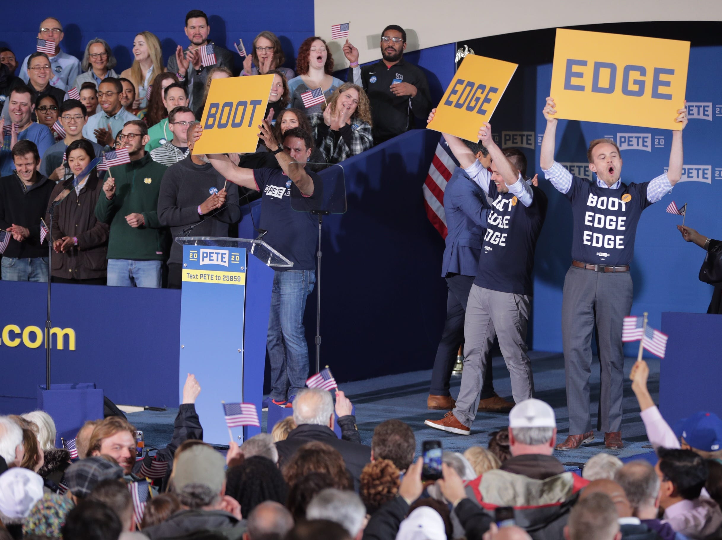 Campaign workers hold up signs with the pronunciation of Pete Buttigieg's last name on Sunday, April 14, 2019, before his announcement in South Bend that he is officially running for president.