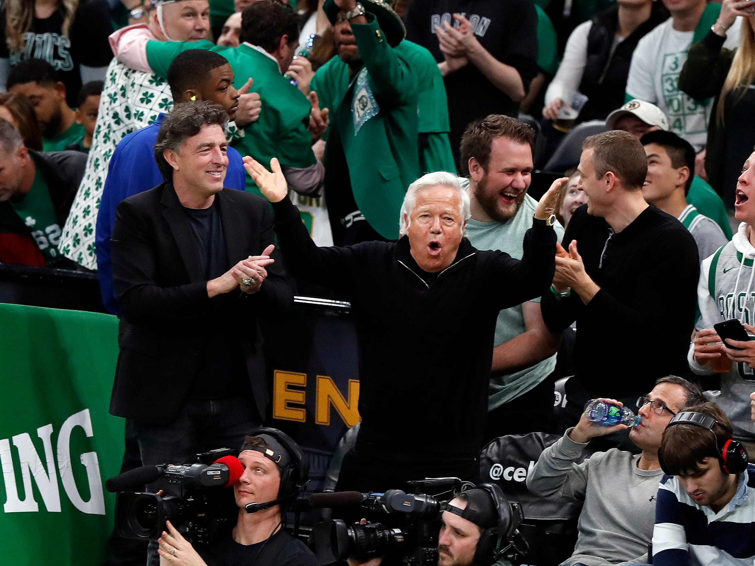 New England Patriots owner Robert Kraft, center, cheers on the Boston Celtics with Celtics owner Wyc Grousbeck, left, during the third quarter in Game 1 of a first-round NBA basketball playoff series between the Celtics and the Indiana Pacers, Sunday, April 14, 2019, in Boston.