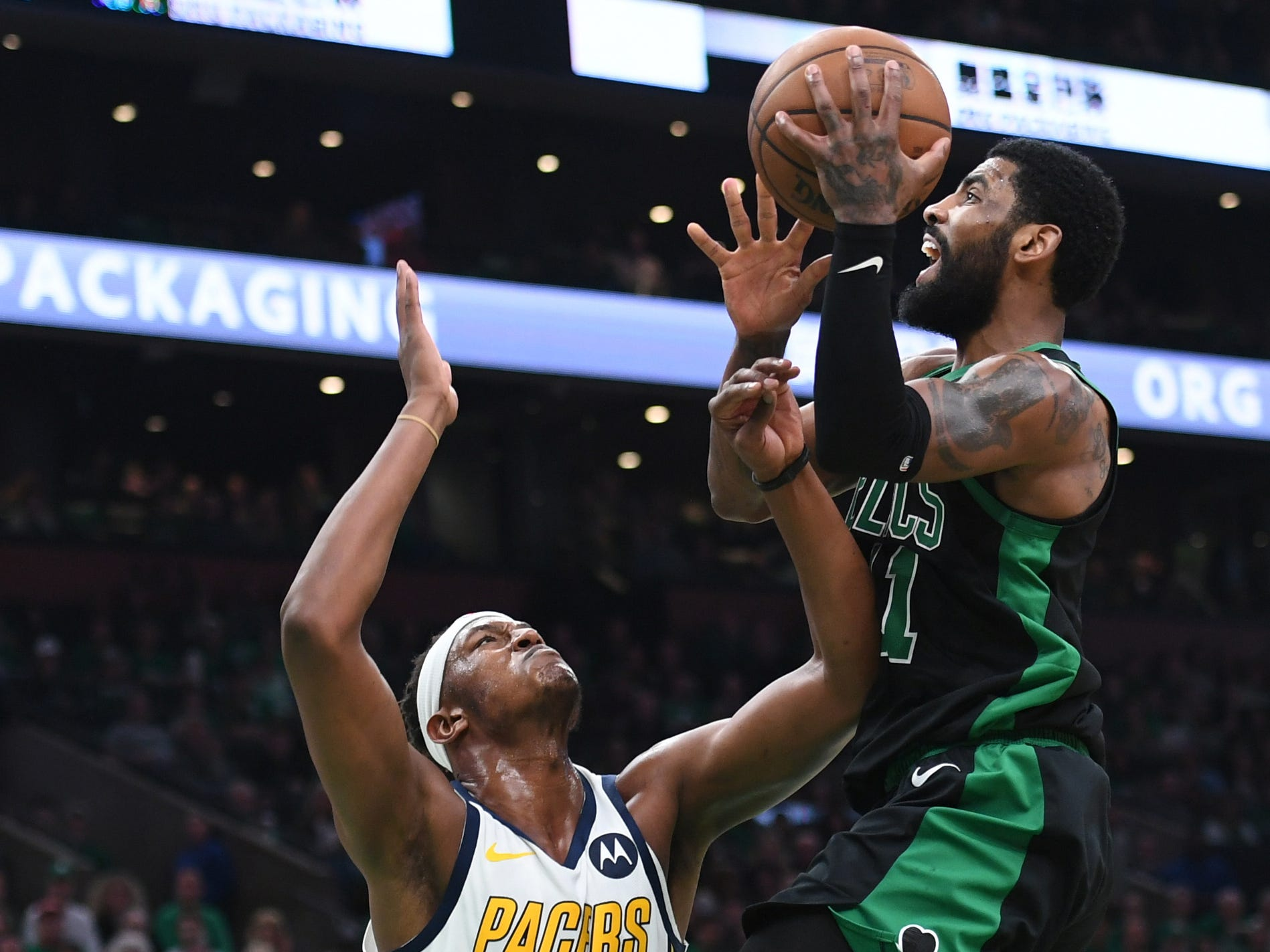 Apr 14, 2019; Boston, MA, USA; Boston Celtics guard Kyrie Irving (11) gets fouled by Indiana Pacers center Myles Turner (33) during the second half in game one of the first round of the 2019 NBA Playoffs at TD Garden.