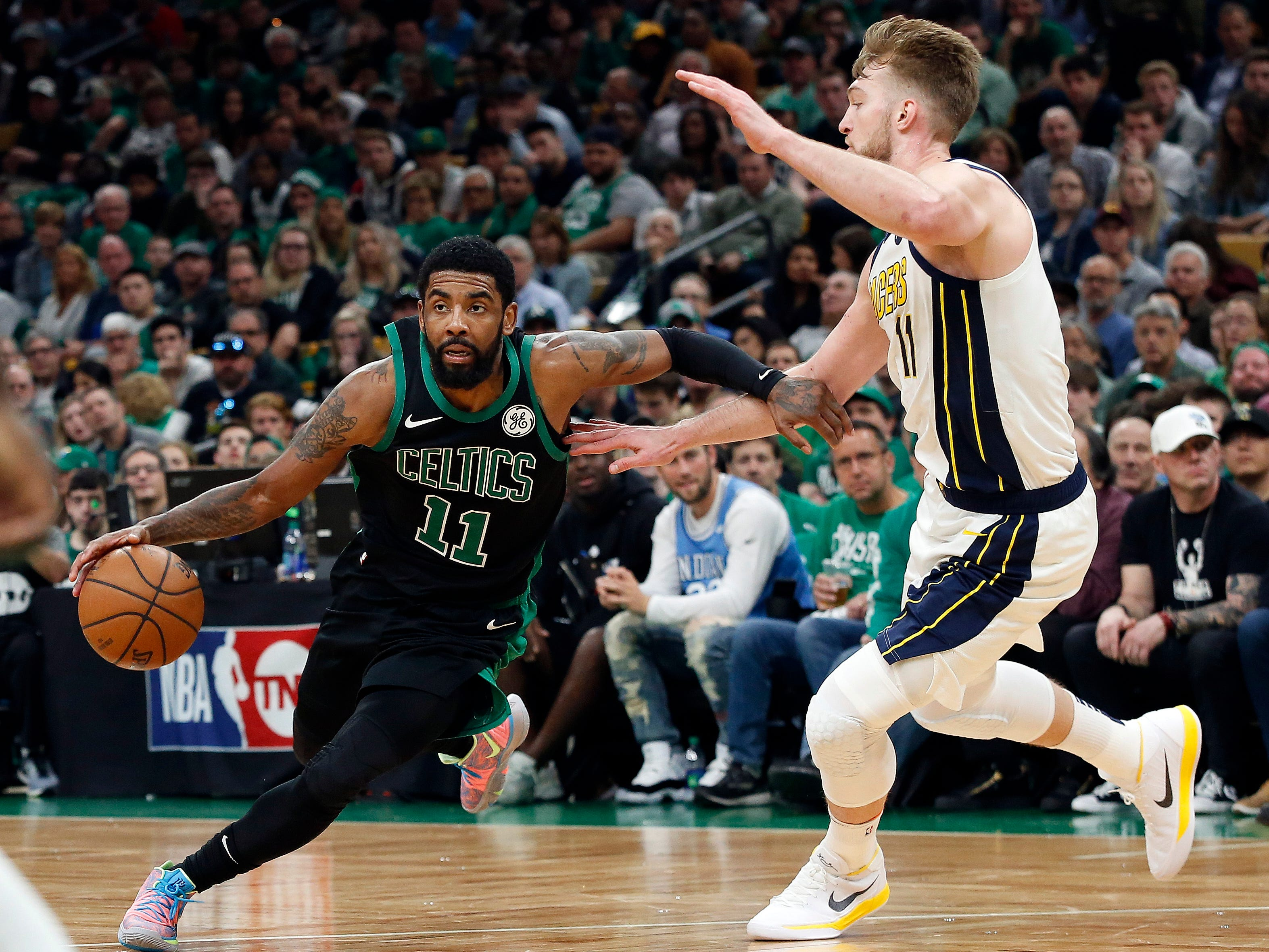 Boston Celtics' Kyrie Irving drives on Indiana Pacers' Domantas Sabonisn during the second quarter in Game 1 of a first-round NBA basketball playoff series, Sunday, April 14, 2019, in Boston.