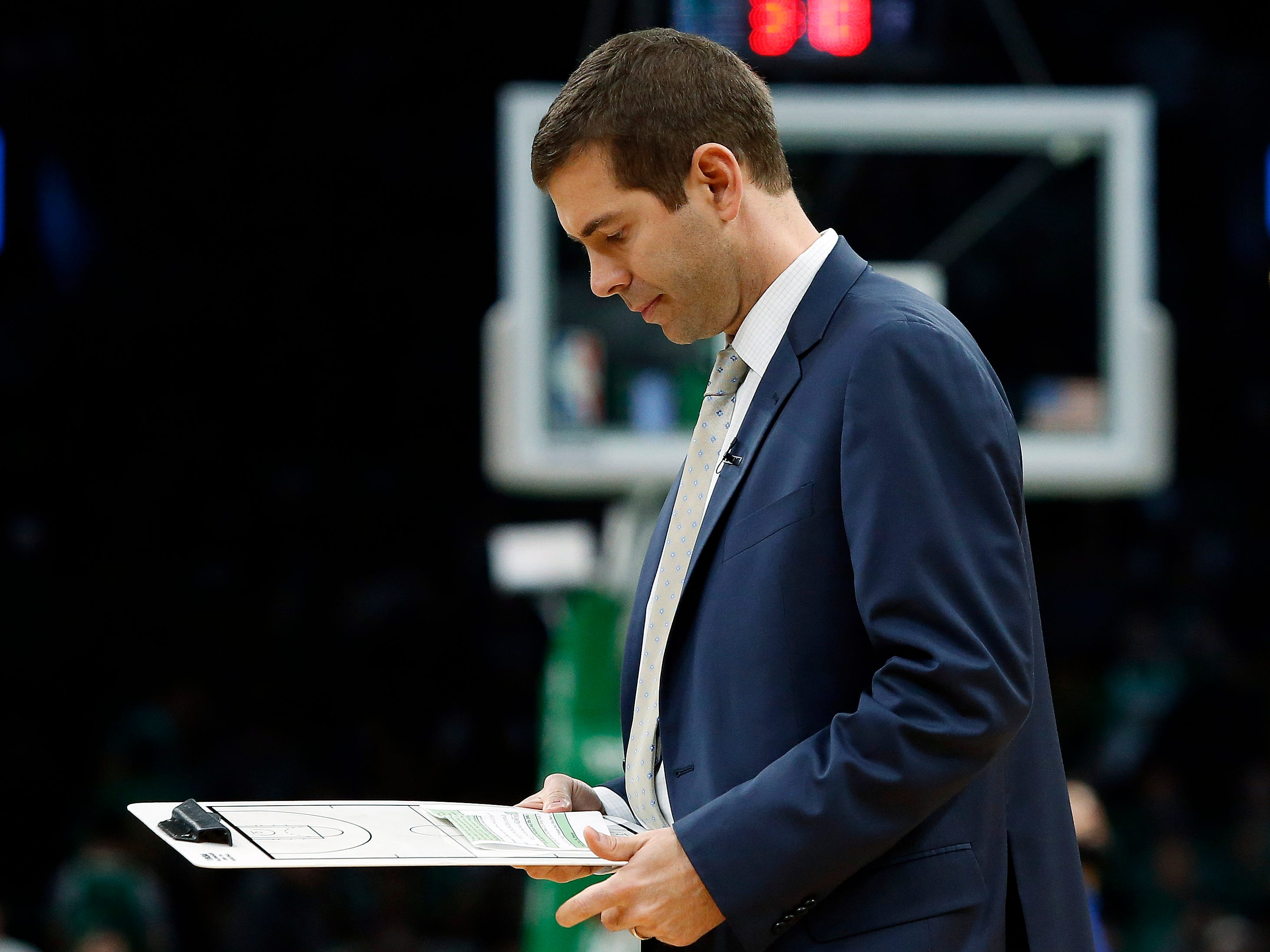 Boston Celtics head coach Brad Stevens looks over his notes during a timeout in the second quarter of Game 1 of a first-round NBA basketball playoff series against the Indiana Pacers, Sunday, April 14, 2019, in Boston.