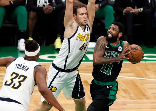 Boston Celtics' Kyrie Irving drives on Indiana Pacers' Bojan Bogdanovic during the first quarter in Game 1 of a first-round NBA basketball playoff series, Sunday, April 14, 2019, in Boston.