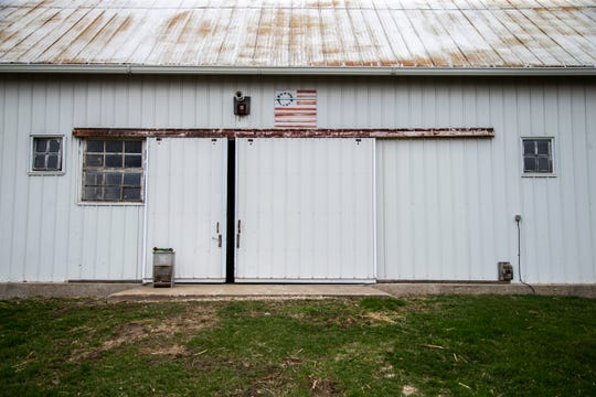A piece of artwork of the American flag hangs above the door to an out building on Friday, April 12, 2019, on the Graham family farm in Poweshiek County, Iowa. The Graham family farms soybeans and corn in addition to raising hogs.