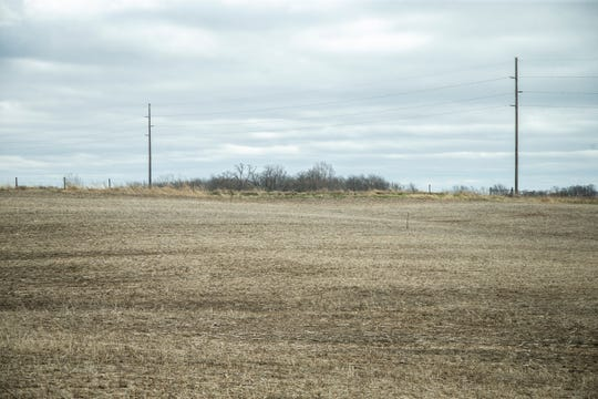 Ground stakes mark the permitter of a new proposed hog confinement building on Friday, April 12, 2019, in a field on the Graham family's property near their home in Poweshiek County, Iowa. The Graham family farms soybeans and corn in addition to raising hogs.