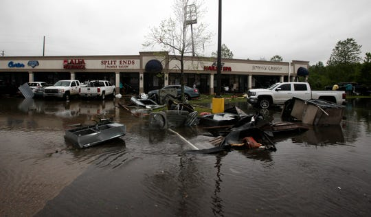 Debris is seen strewn in flooded water in the Pemberton Quarters strip mall following severe weather Saturday, April 13, 2019 in Vicksburg, Miss. Authorities say a possible tornado has touched down in western Mississippi, causing damage to several businesses and vehicles.