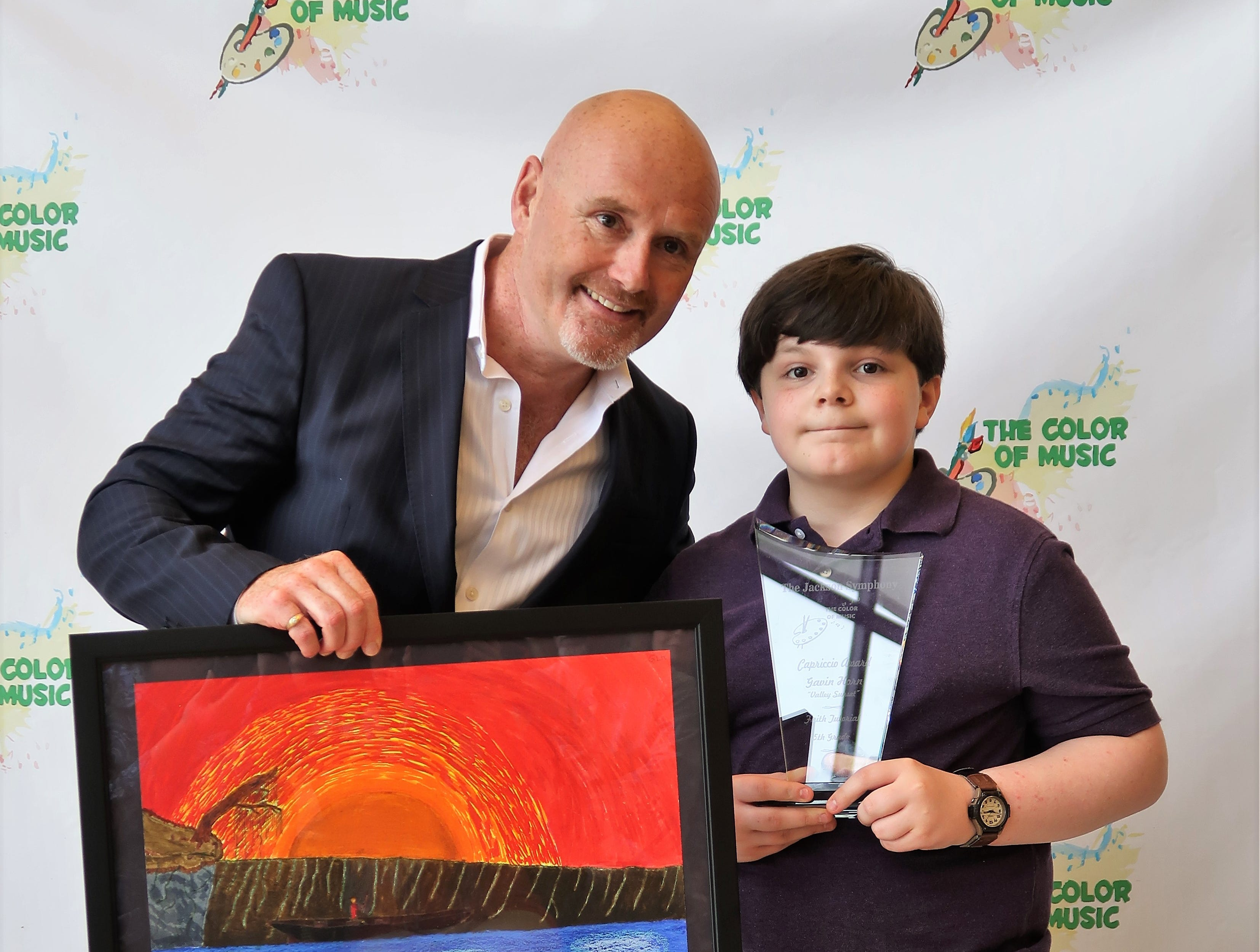 "Fifth-grade student Gavin Horn displays his Capriccio Award for his art piece, ""Valley Sunset,"" alongside Jackson Symphony Director Peter Shannon at the 2019 Color of Music awards at the Carl Perkins Civic Center in Jackson on Saturday, April 13."