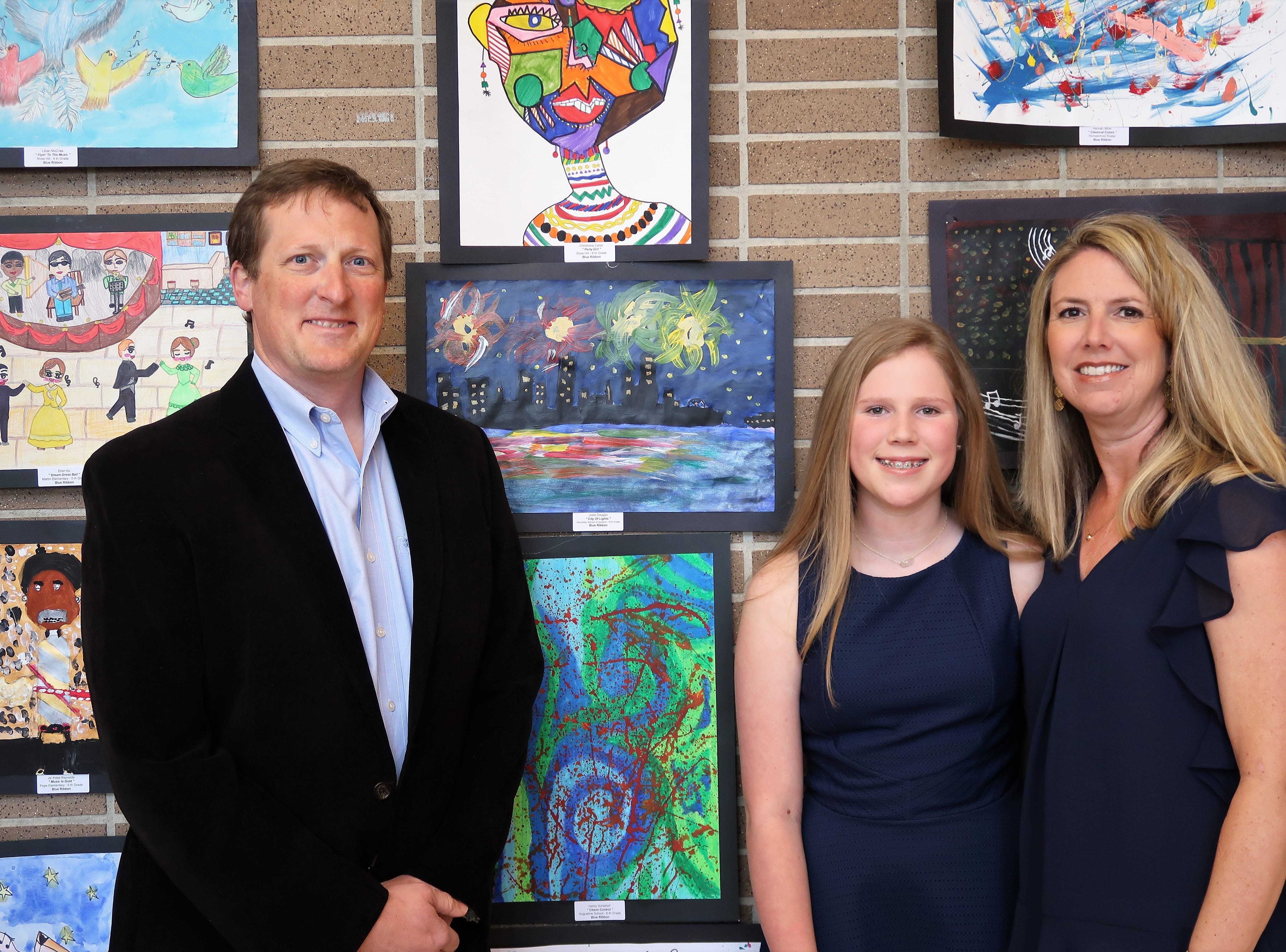 Brian Dougan, Josie Dougan and Amy Dougan pose with Josie's artwork at the 2019 Color of Music awards at the Carl Perkins Civic Center in Jackson on Saturday, April 13.