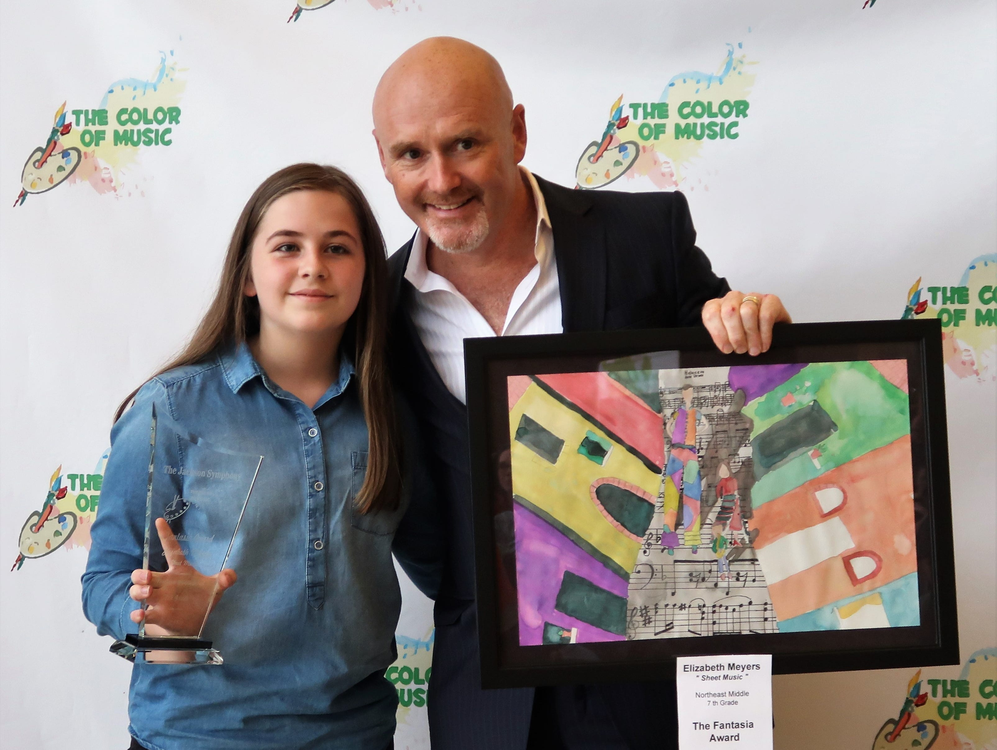 "Seventh-grade student Elizabeth Meyers holds the Fantasia Award, won for her art piece ""Sheet Music,"" next to Jackson Symphony Conductor Peter Shannon at the 2019 Color of Music awards at the Carl Perkins Civic Center in Jackson on Saturday, April 13."