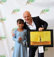 "Third-grade student Nicole Daniel poses with Jackson Symphony Conductor Peter Shannon after winning the Bravo Award for her art piece, ""The Concert"" at the 2019 Color of Music awards at the Carl Perkins Civic Center in Jackson on Saturday, April 13."