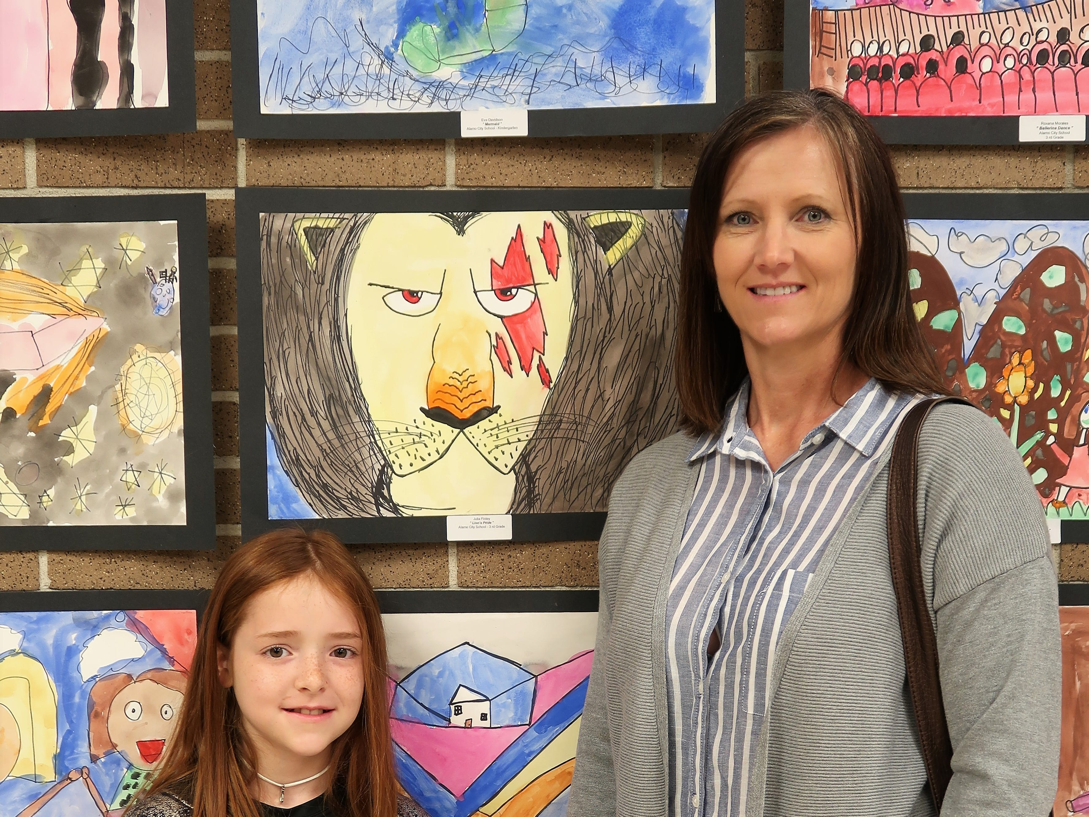 Julia Finley and Angie Smothers pose in front of student artwork at the 2019 Color of Music awards at the Carl Perkins Civic Center in Jackson on Saturday, April 13.