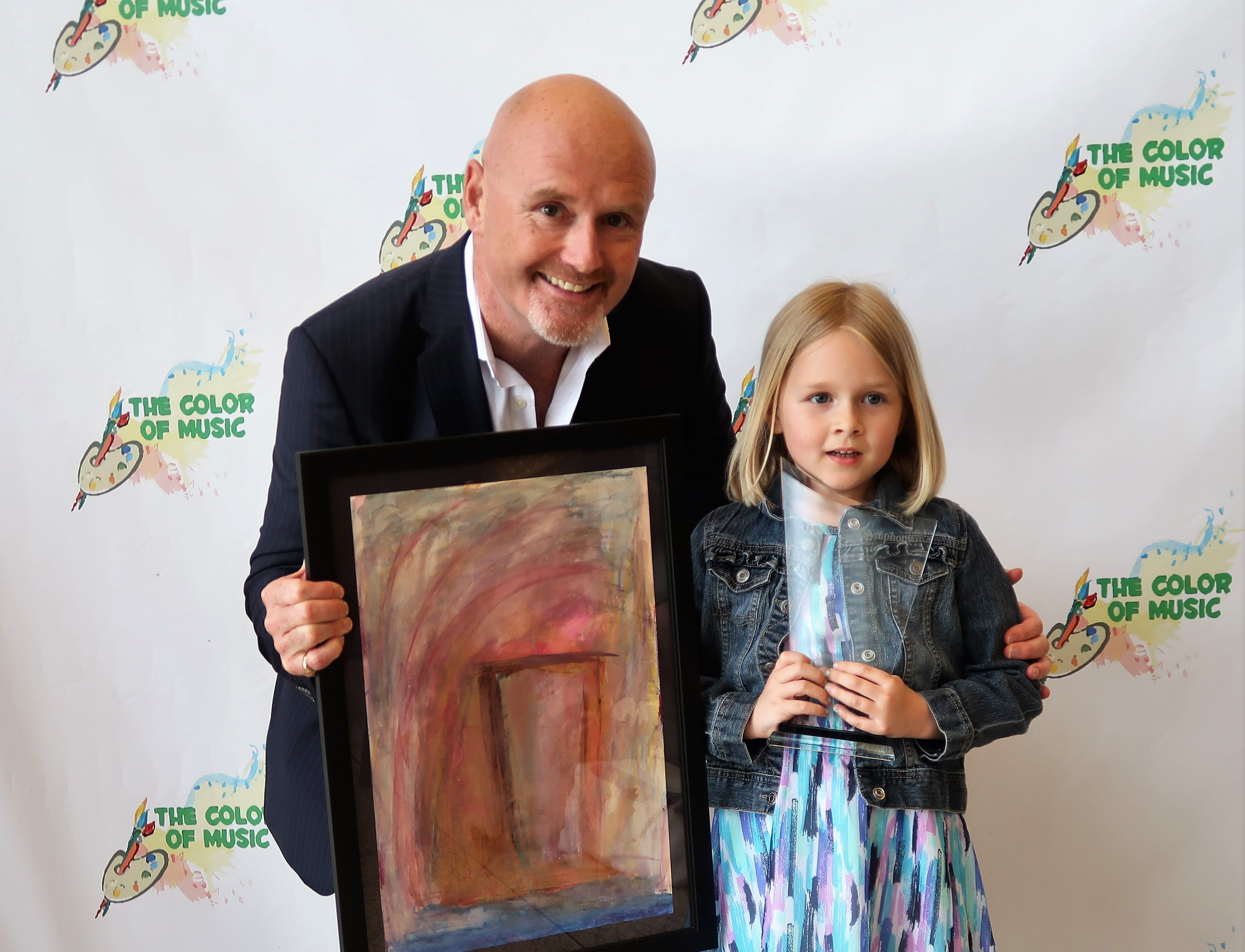 "Kindergartner Lydia Stanley holds her Prelude Award next to Jackson Symphony Conductor Peter Shannon and her painting, ""A Door in the Music,"" at the 2019 Color of Music awards at the Carl Perkins Civic Center in Jackson on Saturday, April 13."
