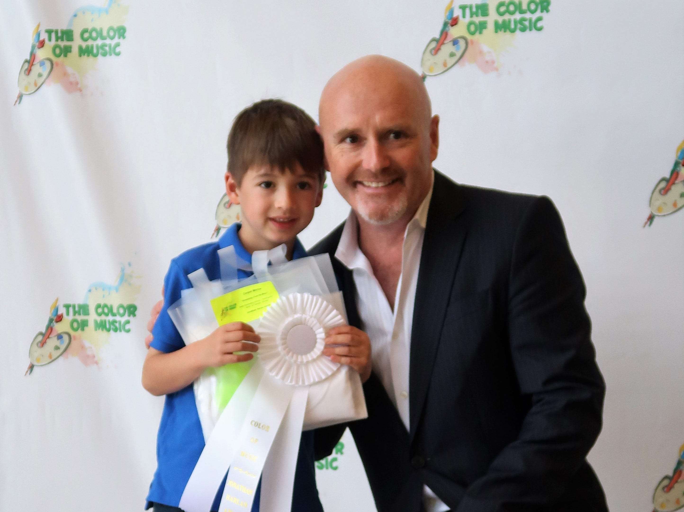 Cooper Morrow smiles next to Jackson Symphony Conductor Peter Shannon after receiving an award for his artwork at the 2019 Color of Music awards at the Carl Perkins Civic Center in Jackson on Saturday, April 13.