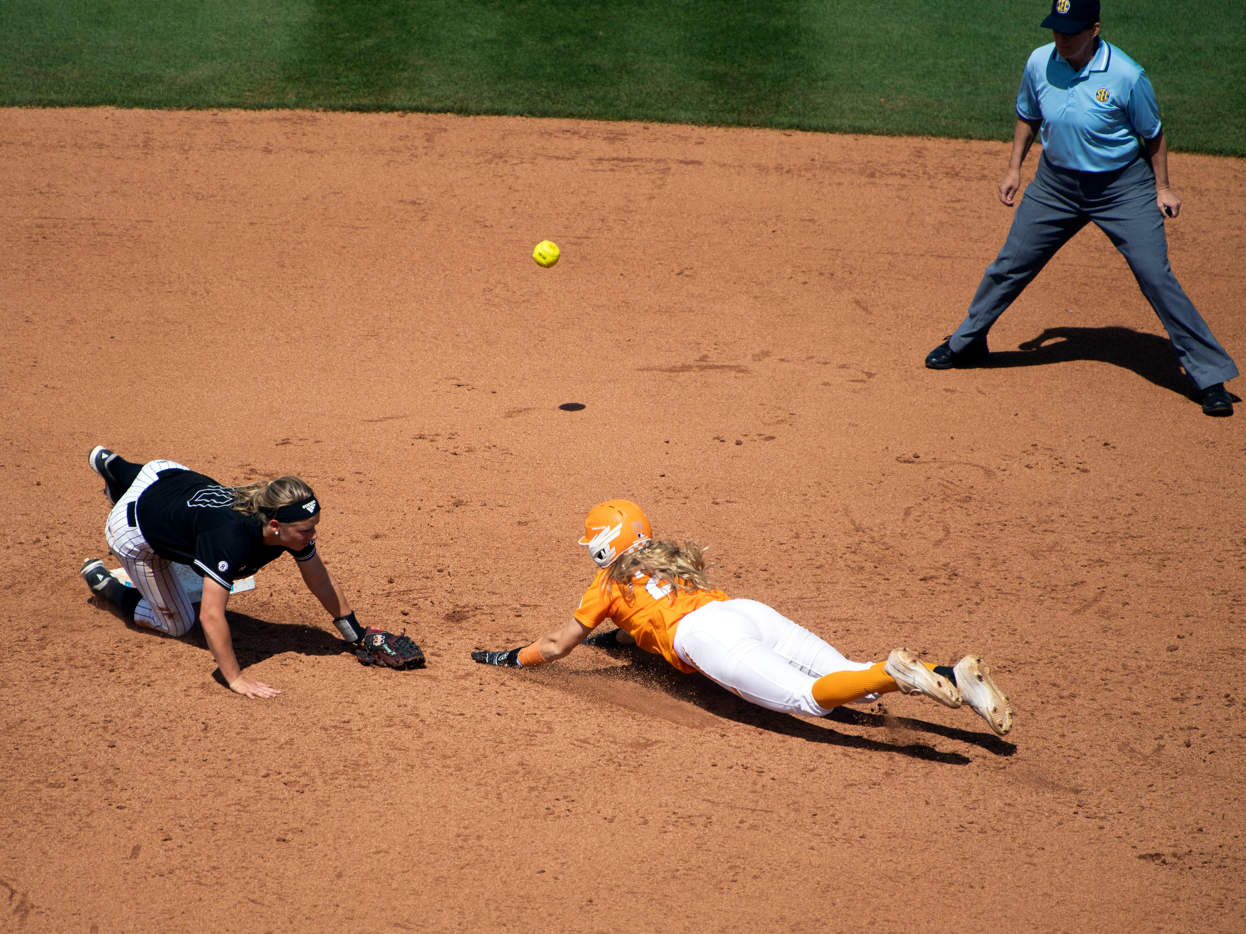 The ball flies past Mississippi State's Kinsey Goelz (10) and Tennessee's Cailin Hannon (24) slides safely to second base at Sherri Parker Lee Stadium on Sunday, April 14, 2019.