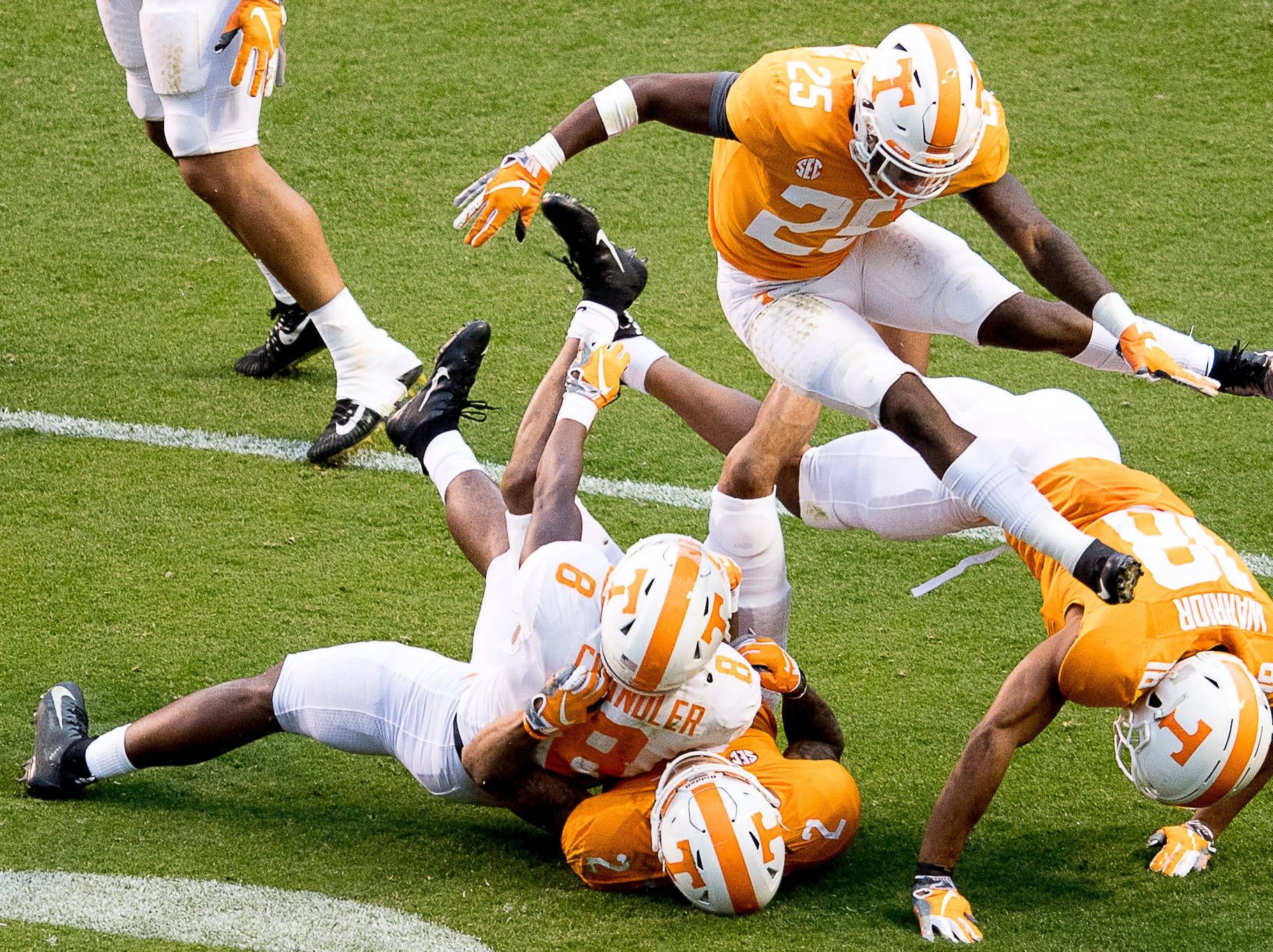 Tennessee defensive back Trevon Flowers (25) leaps over Tennessee running back Ty Chandler (8), Tennessee defensive back Alontae Taylor (2) and Tennessee defensive back Nigel Warrior (18) during the Tennessee Spring Game at Neyland Stadium in Knoxville, Tennessee on Saturday, April 13, 2019.