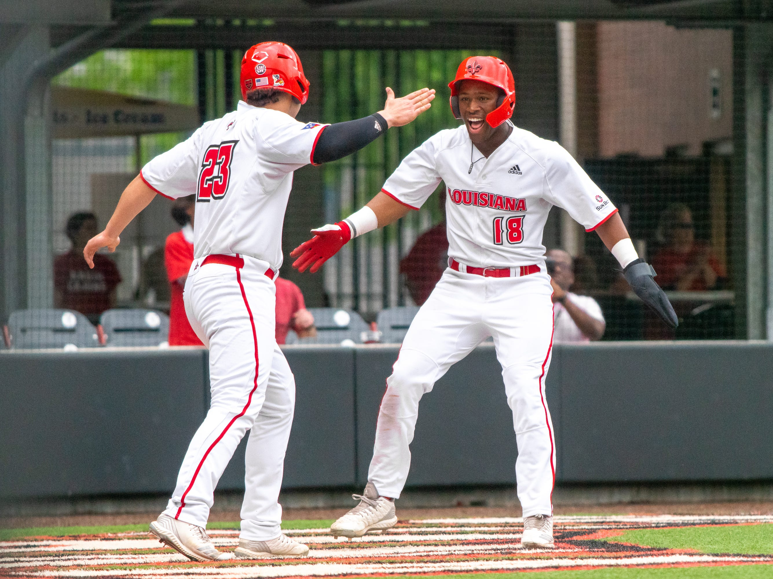 """UL's Handsome Monica (23) and Tremaine Spears (18) celebrate their two-run score as the Ragin' Cajuns take on the South Alabama Jaguars at M.L. """"Tigue"""" Moore Field on Saturday, April 13, 2019."""