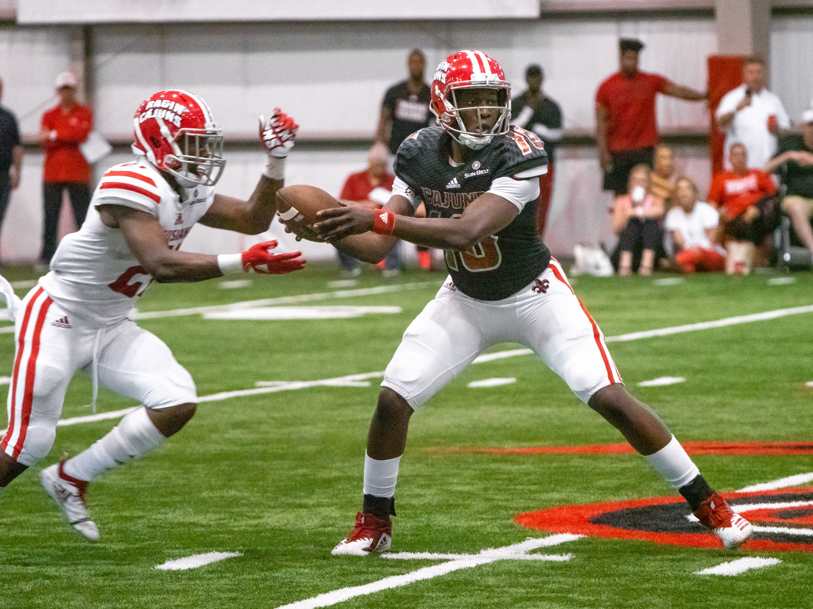 UL's quarterback Clifton McDowell hands off the ball during the play as the Ragin' Cajuns football team plays their annual Spring football game against one another in the Leon Moncla trainig facility on April 13, 2019.