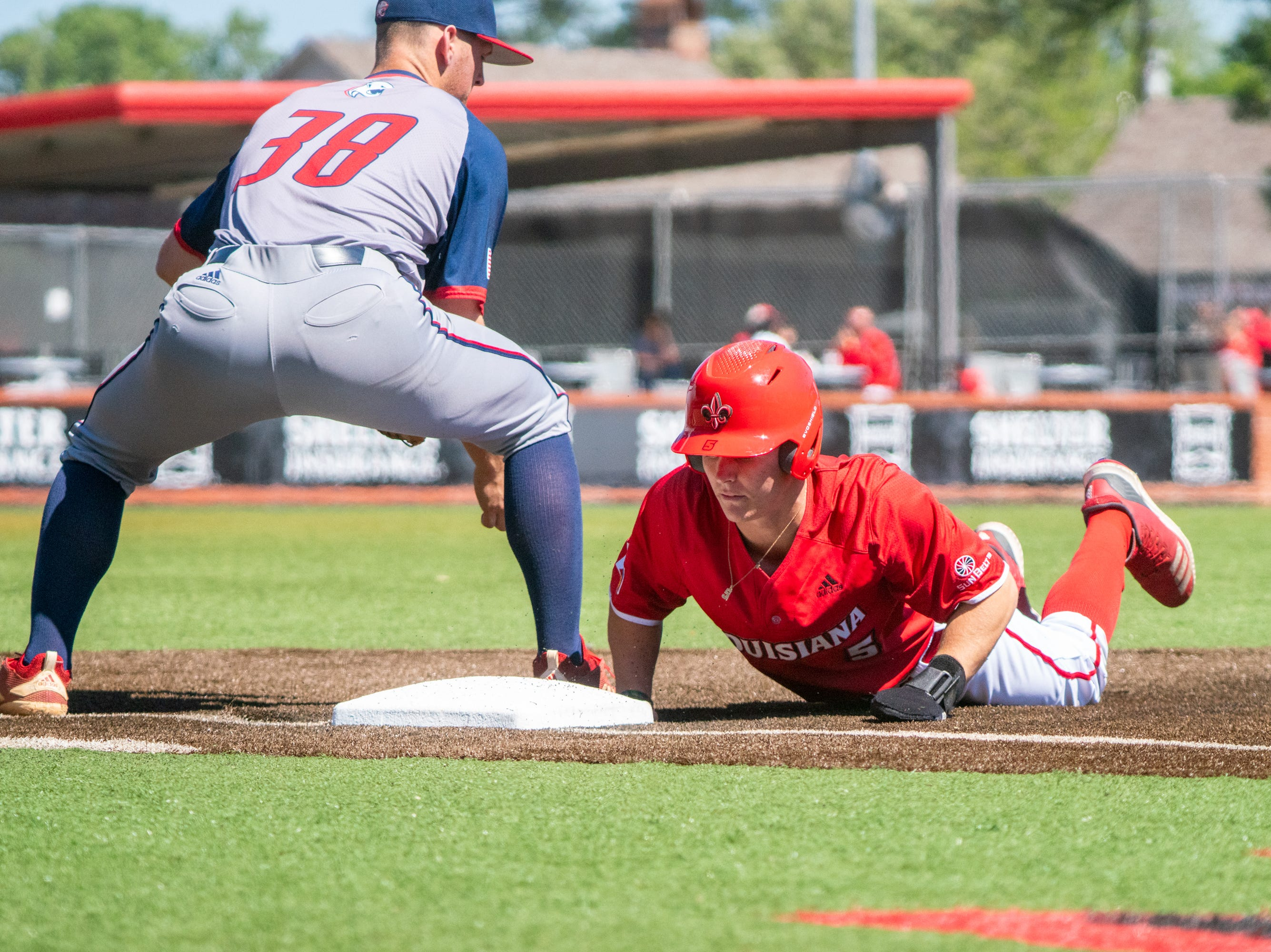 """UL's Hayden Cantrelle dives back onto first base to get safe as the Ragin' Cajuns take on the South Alabama Jaguars at M.L. """"Tigue"""" Moore Field on Sunday, April 14, 2019."""