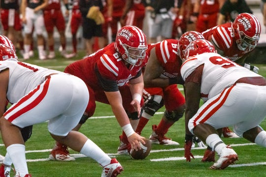 Ragin' Cajuns center Cole Prudhomme (with ball) and guard Ken Marks (67), shown here during UL's 2019 spring game, both are expected to return this year after their senior seasons were derailed by knee injuries.