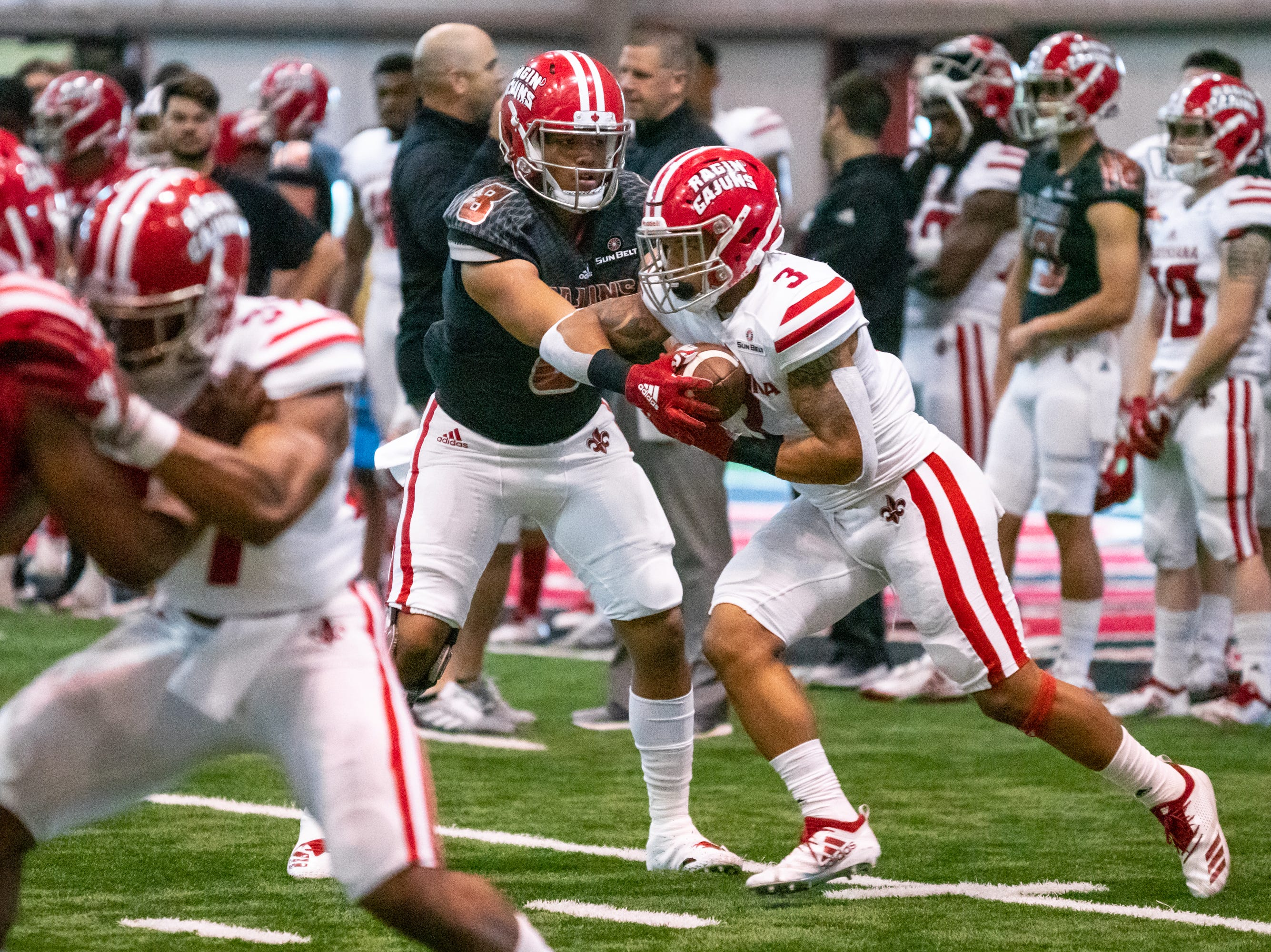 UL's quarterback Jai'ave Magalei hands off the ball during the play as the Ragin' Cajuns football team plays their annual Spring football game against one another in the Leon Moncla trainig facility on April 13, 2019.