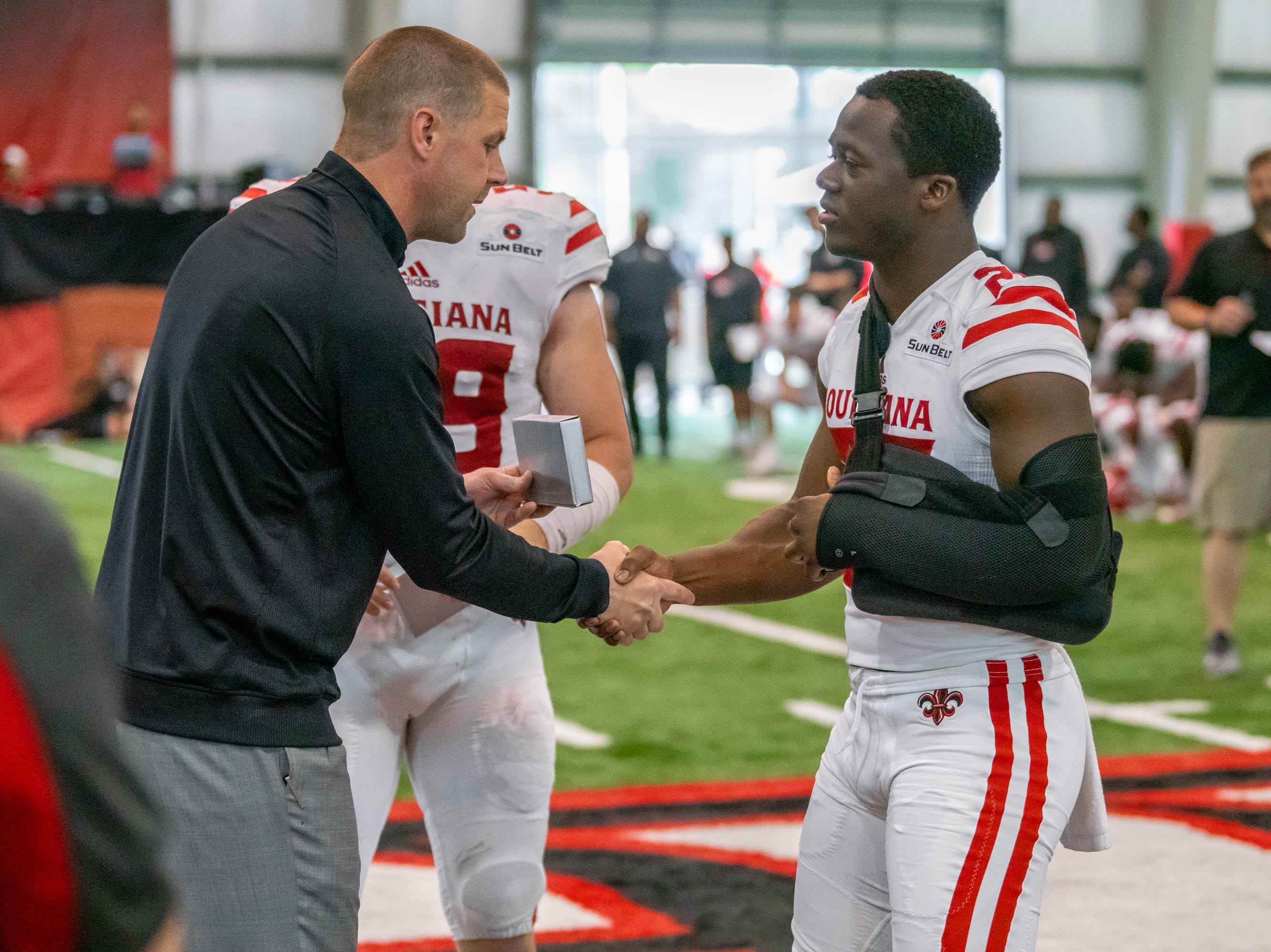 UL's head coach Billy Napier shakes hands with Deuce Wallace as the Ragin' Cajuns football team plays their annual Spring football game against one another in the Leon Moncla trainig facility on April 13, 2019.
