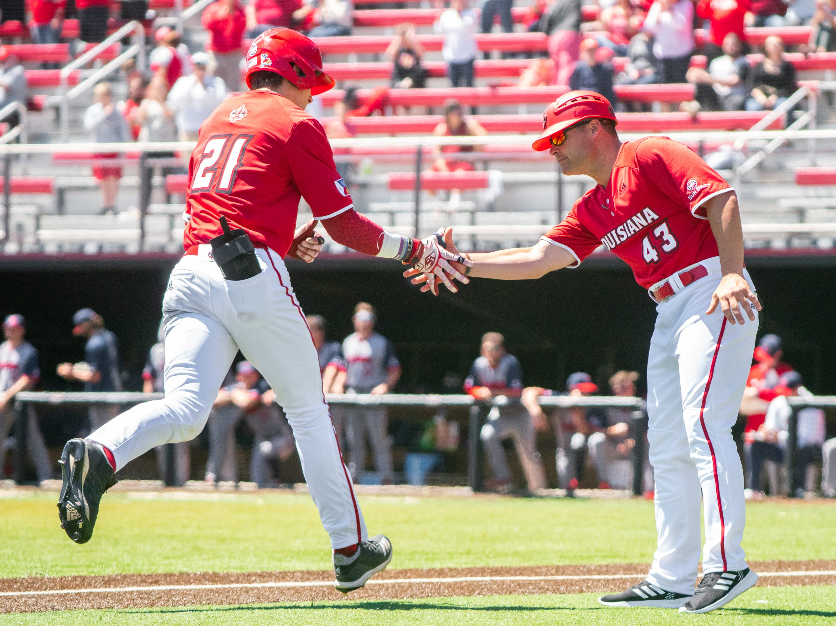 """UL's assistant coach Jake Wells (43) congratulates Orynn Veillon (21) after his homerun hit as the Ragin' Cajuns take on the South Alabama Jaguars at M.L. """"Tigue"""" Moore Field on Sunday, April 14, 2019."""