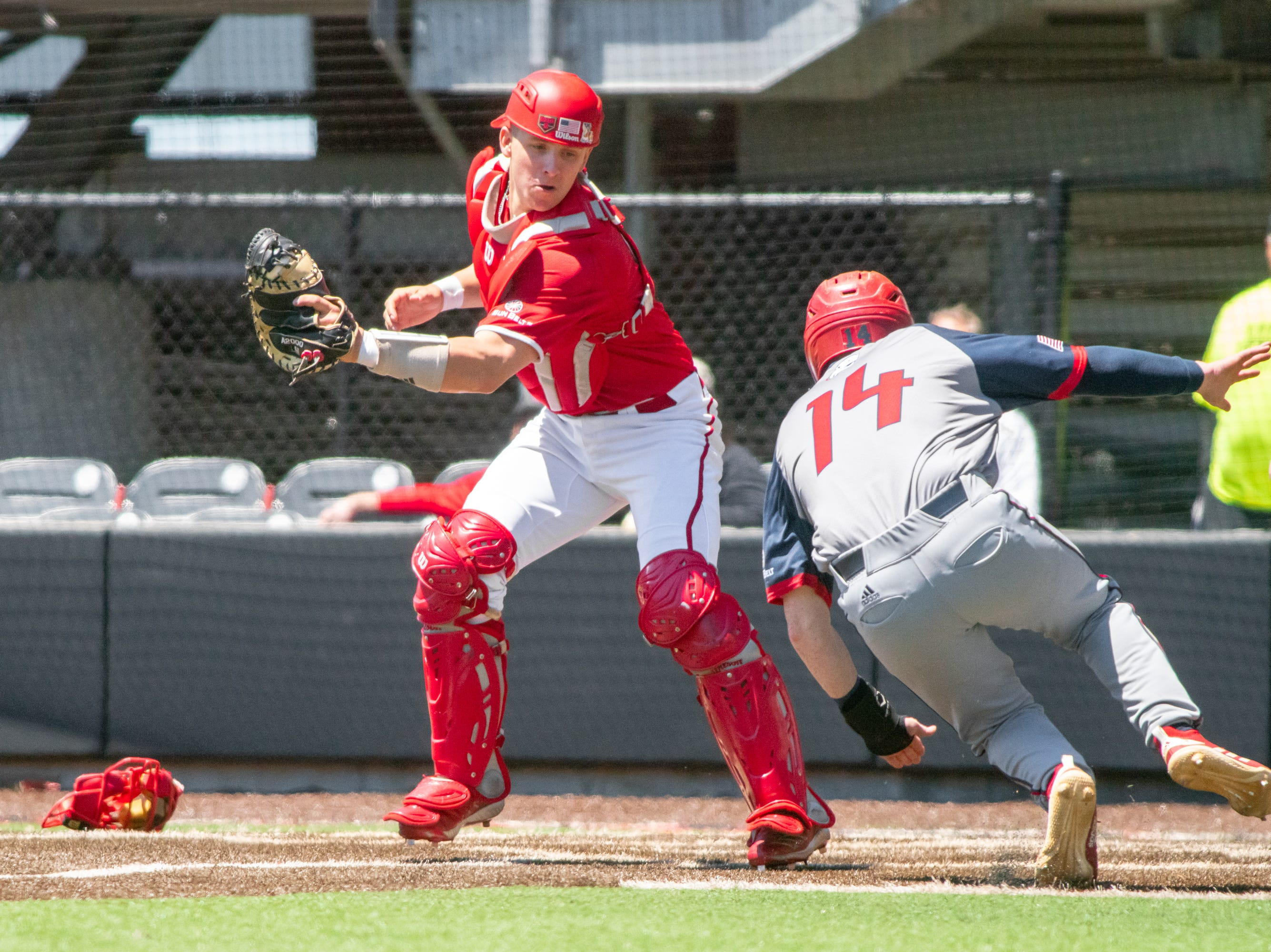 """UL's catcher Kole McKinnon attempts to get the runner out at home plate as the Ragin' Cajuns take on the South Alabama Jaguars at M.L. """"Tigue"""" Moore Field on Sunday, April 14, 2019."""
