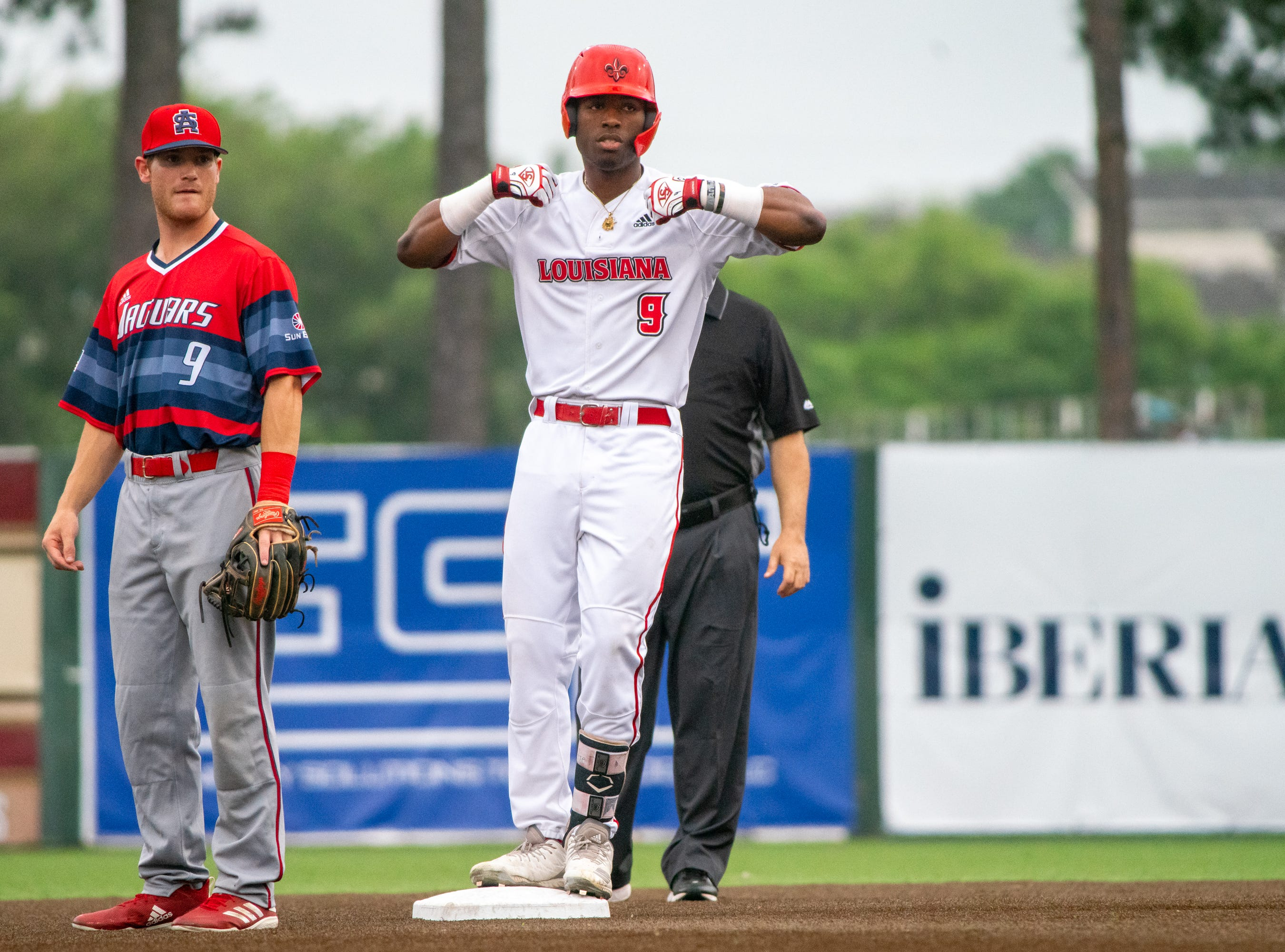 """UL's Todd Lott celebrates his hit on second base as the Ragin' Cajuns take on the South Alabama Jaguars at M.L. """"Tigue"""" Moore Field on Saturday, April 13, 2019."""
