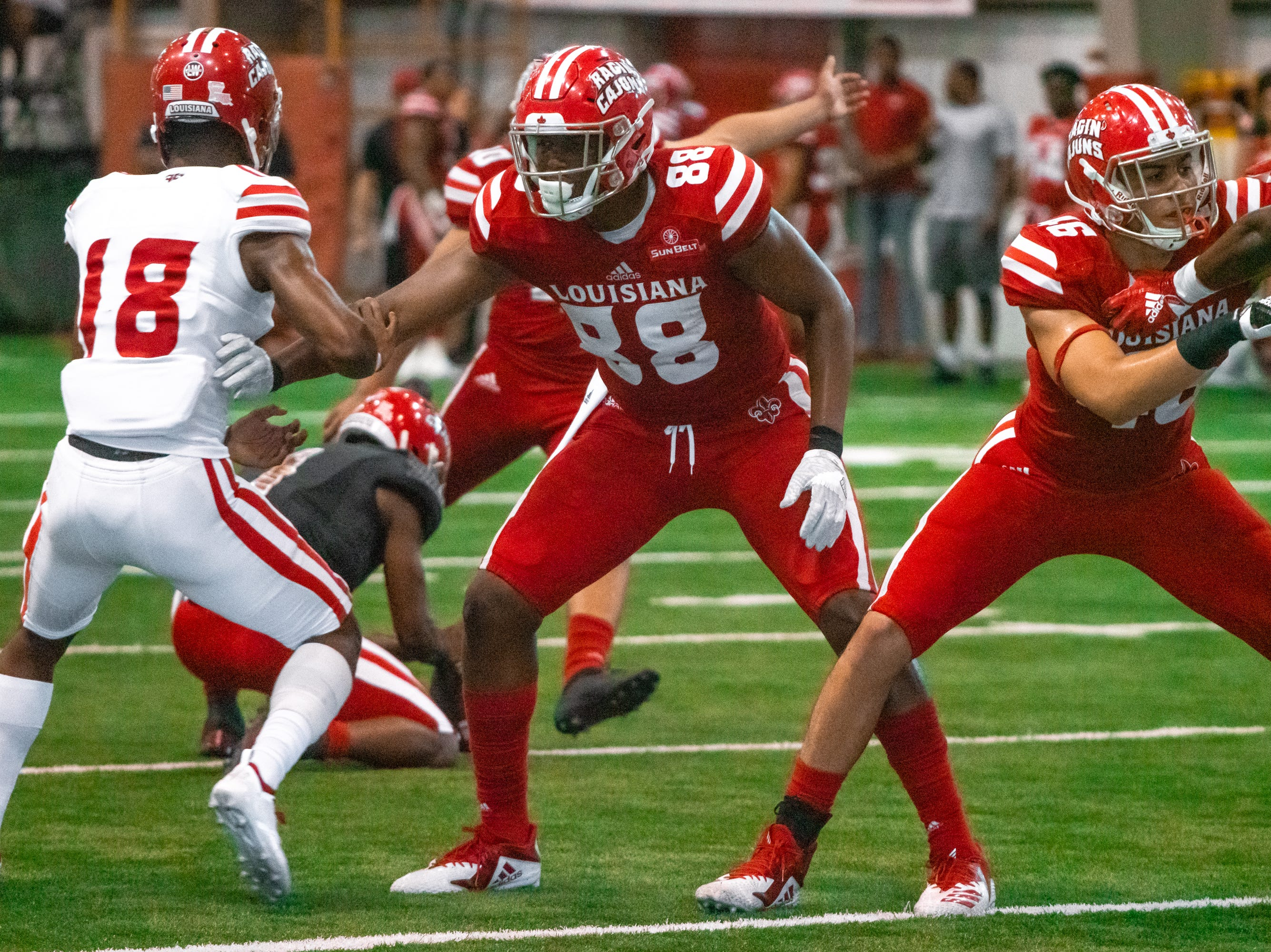 UL's Johnny Lumpkin (88) holds the defense back as the Ragin' Cajuns football team plays their annual Spring football game against one another in the Leon Moncla trainig facility on April 13, 2019.