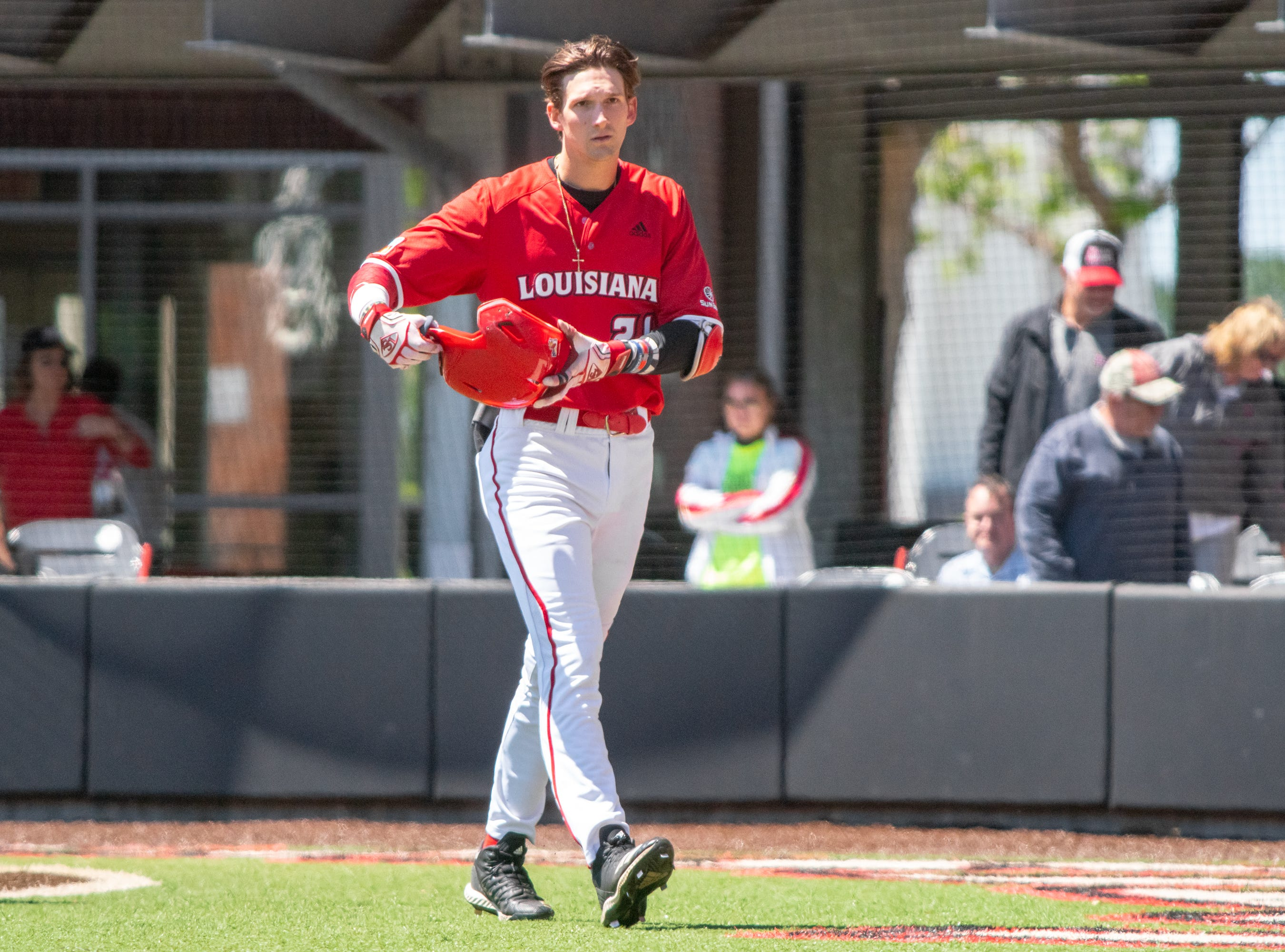 """UL's Orynn Veillon celebrates his score while walking to the dugout as the Ragin' Cajuns take on the South Alabama Jaguars at M.L. """"Tigue"""" Moore Field on Sunday, April 14, 2019."""