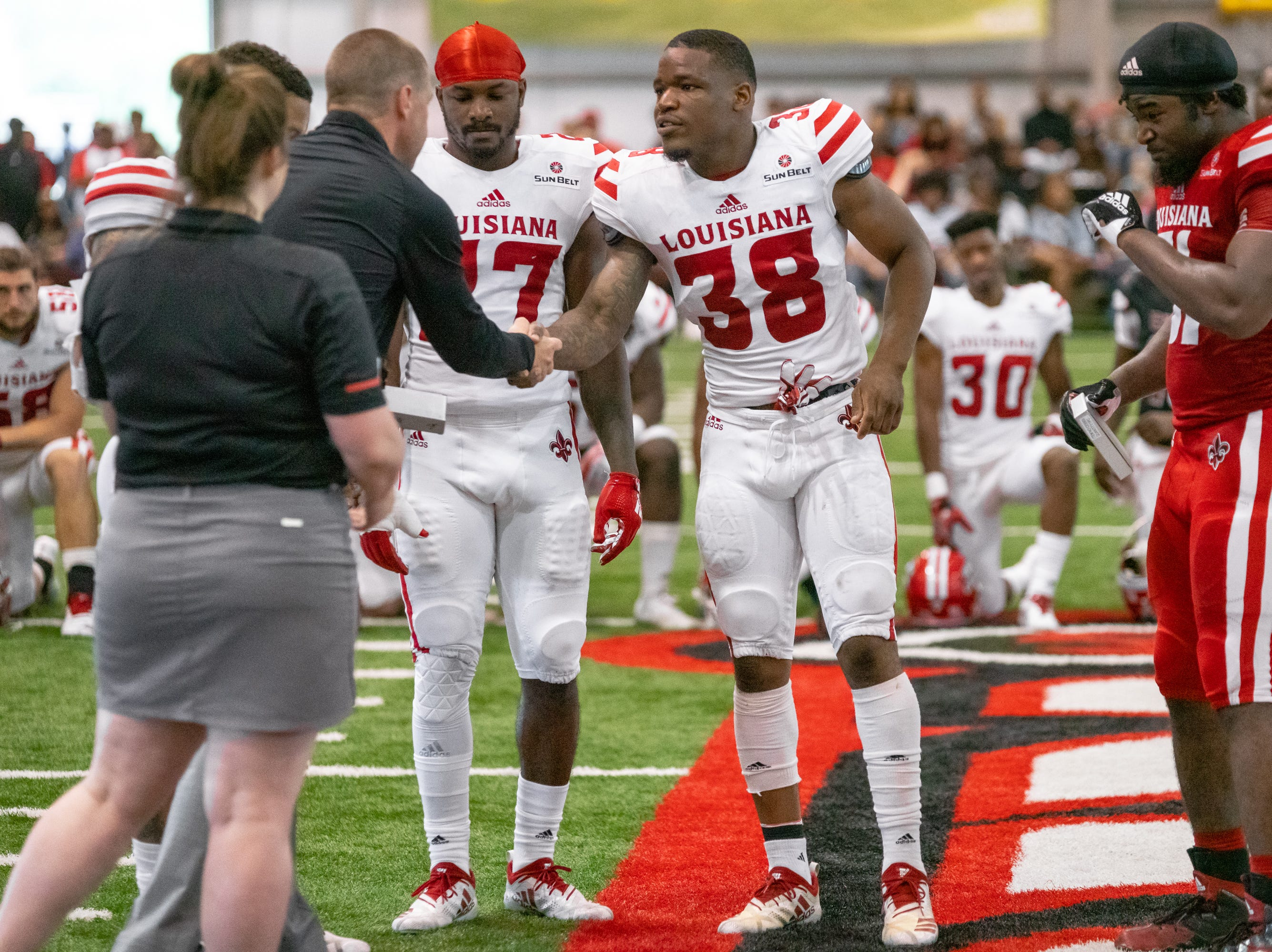 UL's Terik Miller shakes hands with head coach Billy Napier during halftime as the Ragin' Cajuns football team plays their annual Spring football game against one another in the Leon Moncla trainig facility on April 13, 2019.