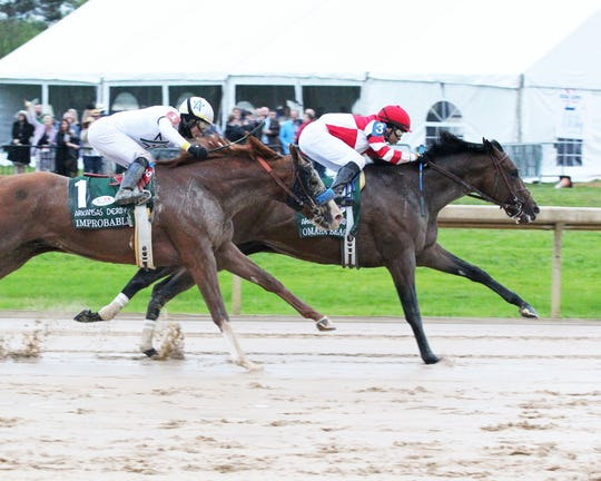 Omaha Beach and jockey Mike Smith hold off Improbable and jockey Jose Ortiz to win the Arkansas Derby on April 13 at Oaklawn Park in Hot Springs, Ark.