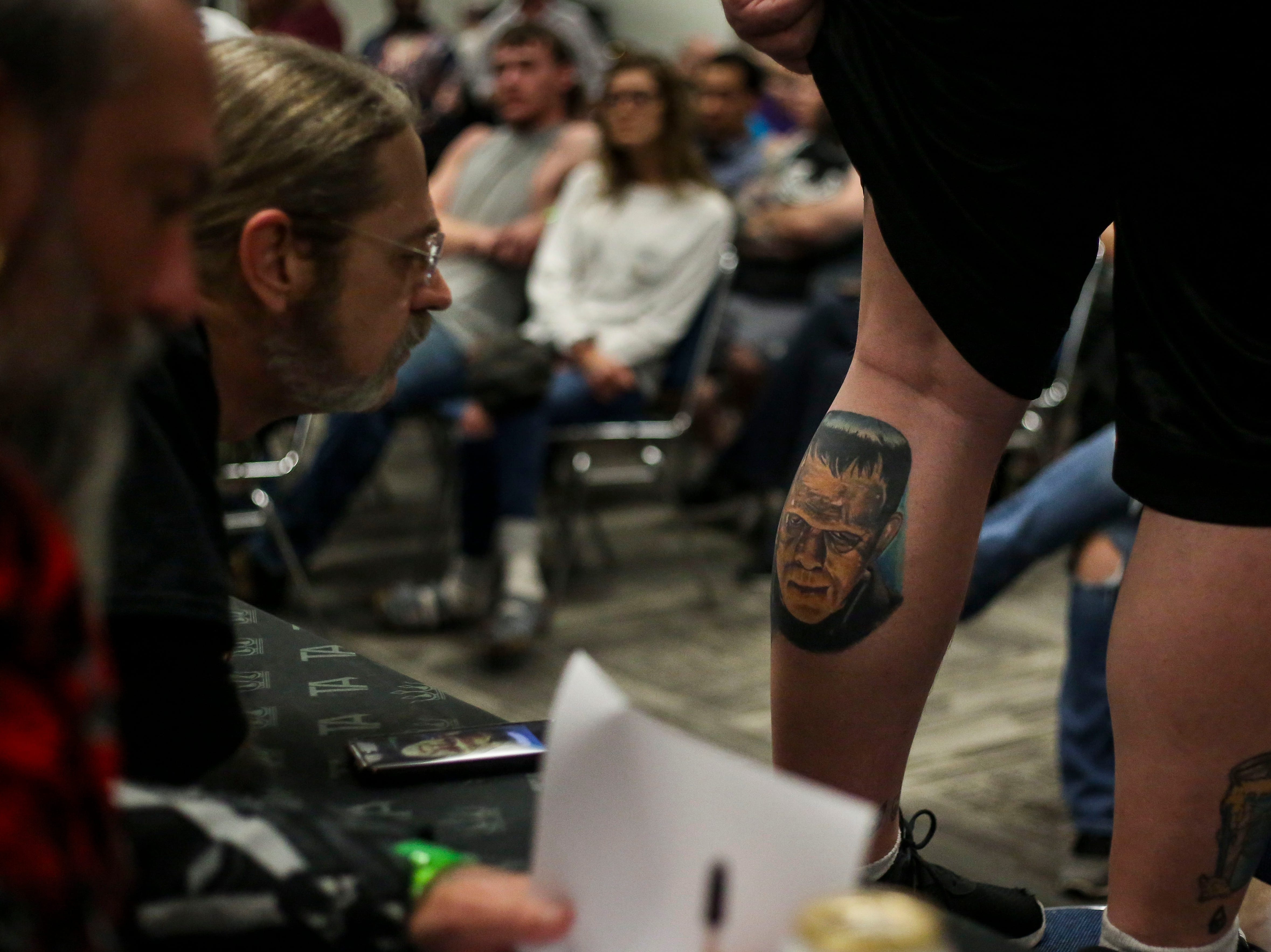 Troy Timpel, Villain Arts, left, judges Chuck Wilcox's Frankenstein tattoo during the tattoo contest at the 8th Annual Louisville Tattoo Arts Convention put on by Villain Arts at the Kentucky Expo Center in Louisville, Ky. on Saturday, April 13, 2019.
