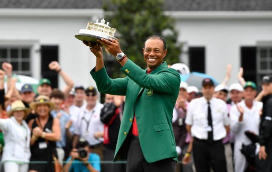 Tiger Woods celebrates with the green jacket and trophy after winning The Masters golf tournament at Augusta National Golf Club in Augusta, Georgia, on Sunday, April 14, 2019.