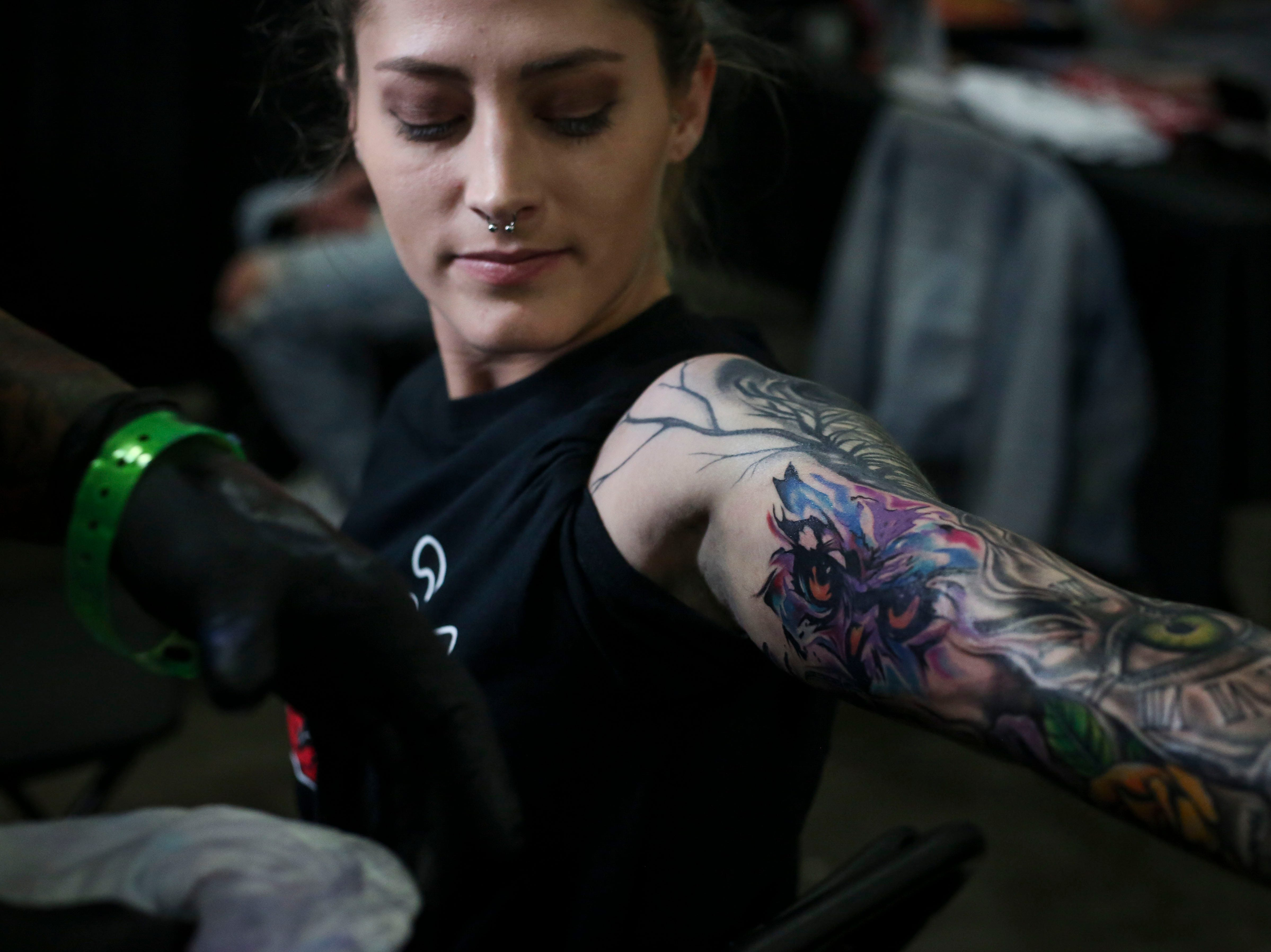 Alonzo Chappell cleans up Michelle Adwell's tattoos ahead of the tattoo contest during the 8th Annual Louisville Tattoo Arts Convention put on by Villain Arts at the Kentucky Expo Center in Louisville, Ky. on Saturday, April 13, 2019.